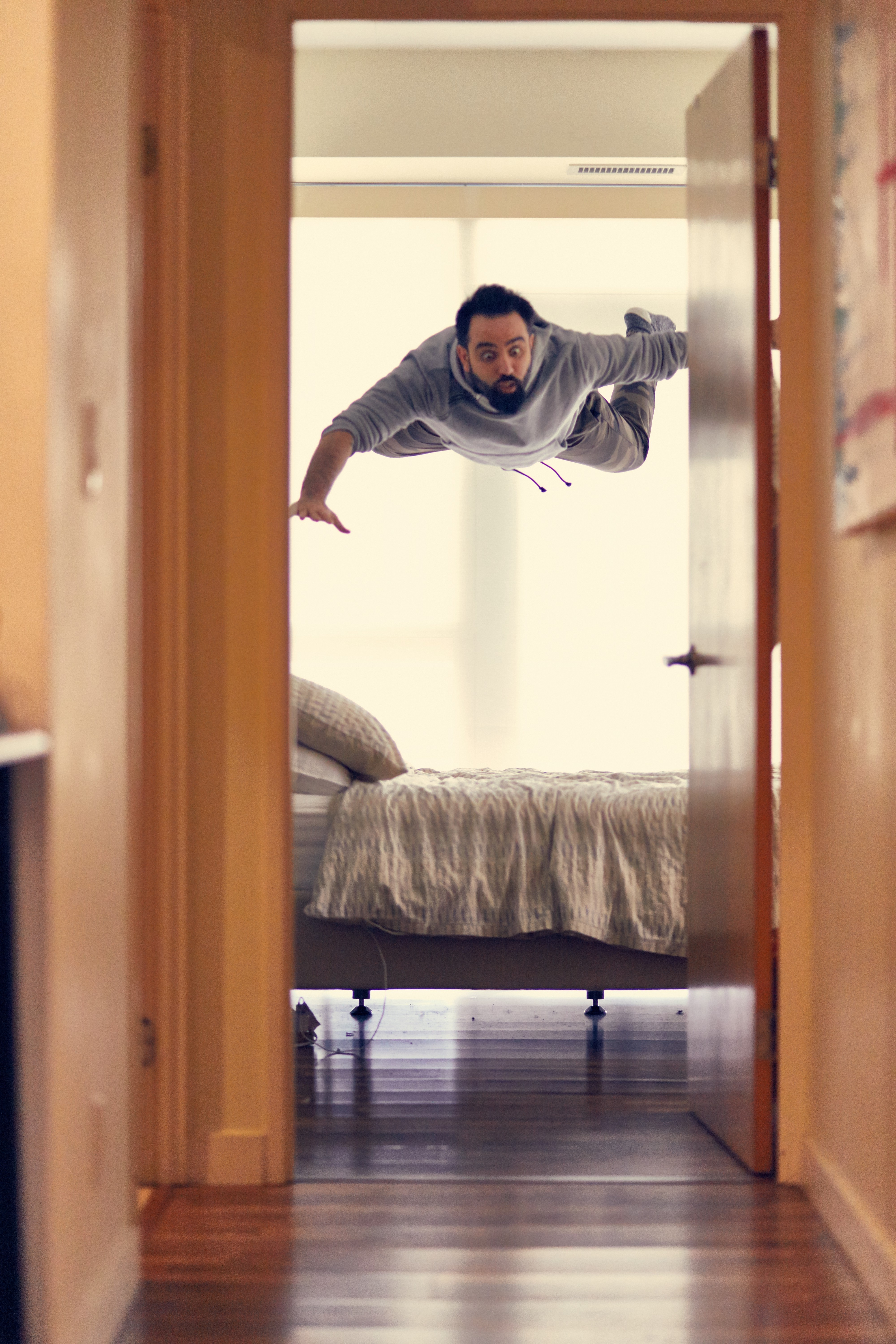Picture of a man with a surpised look falling towards a bed