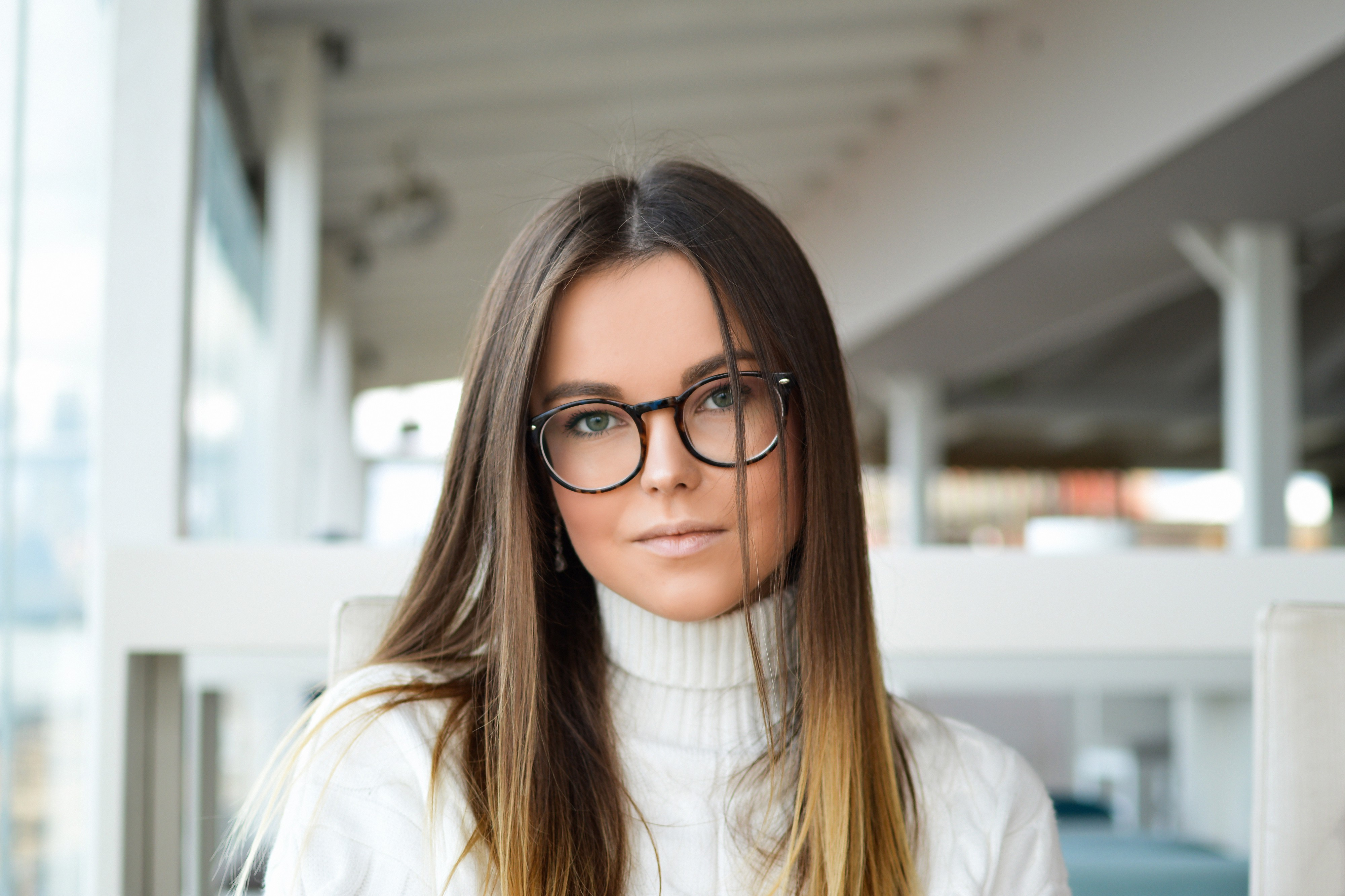 A woman with long, brown hair and round glasses looks into the camera. She is wearing a white, turtle neck sweater.