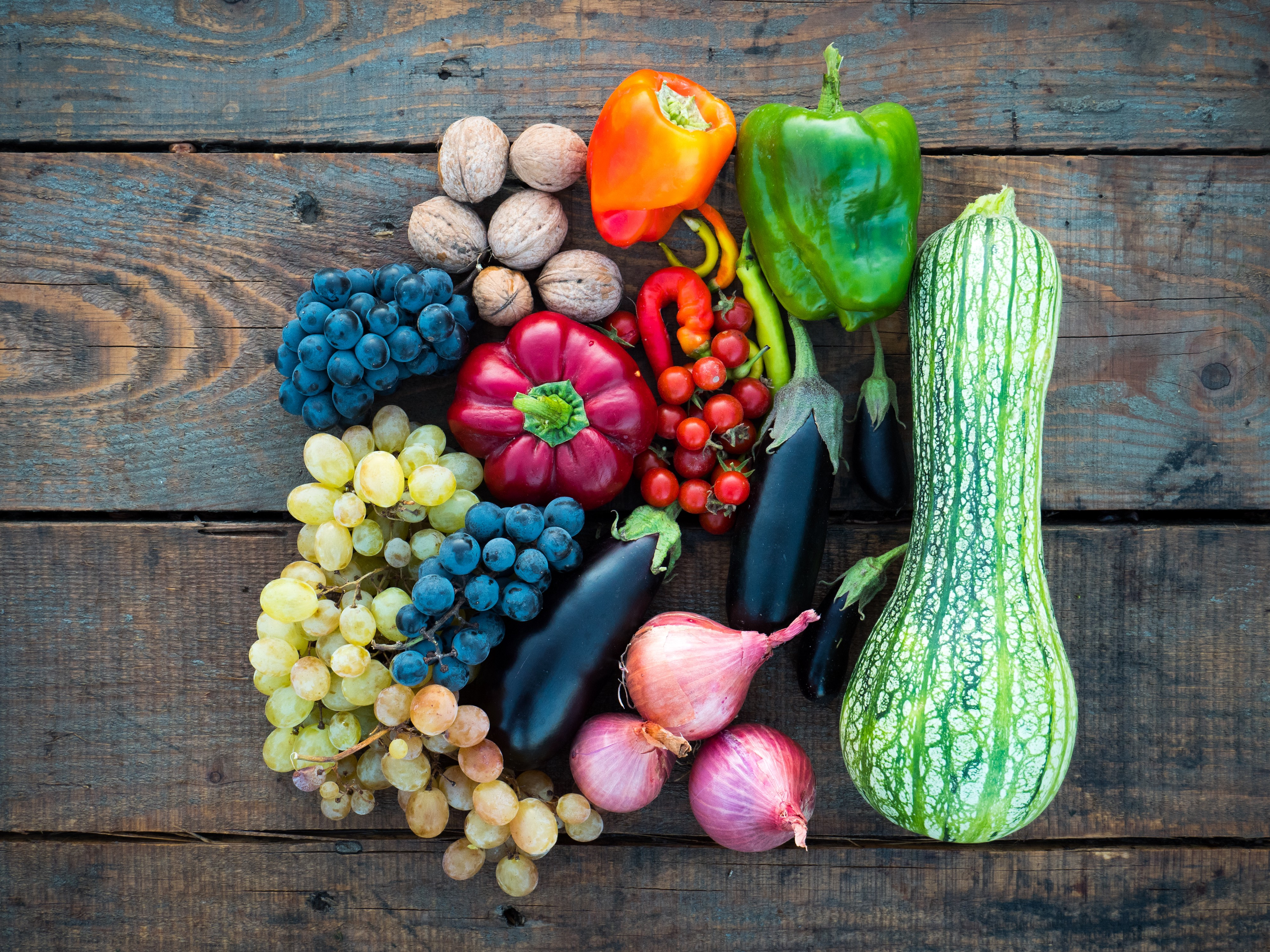 Overhead shot of fruits and vegetables on a distressed wooden table.