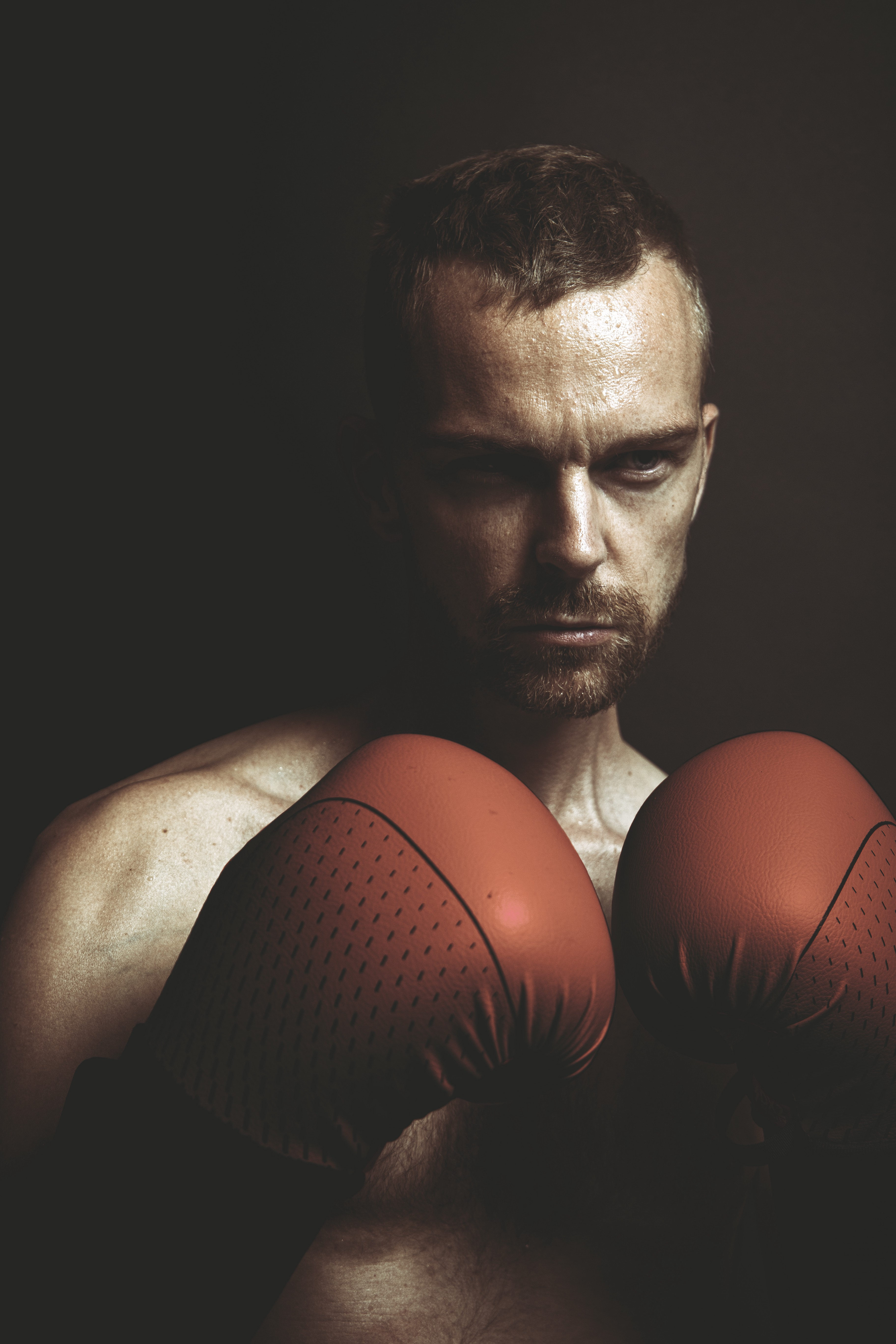 Close up of a handsome man bare chested, wearing boxing gloves.