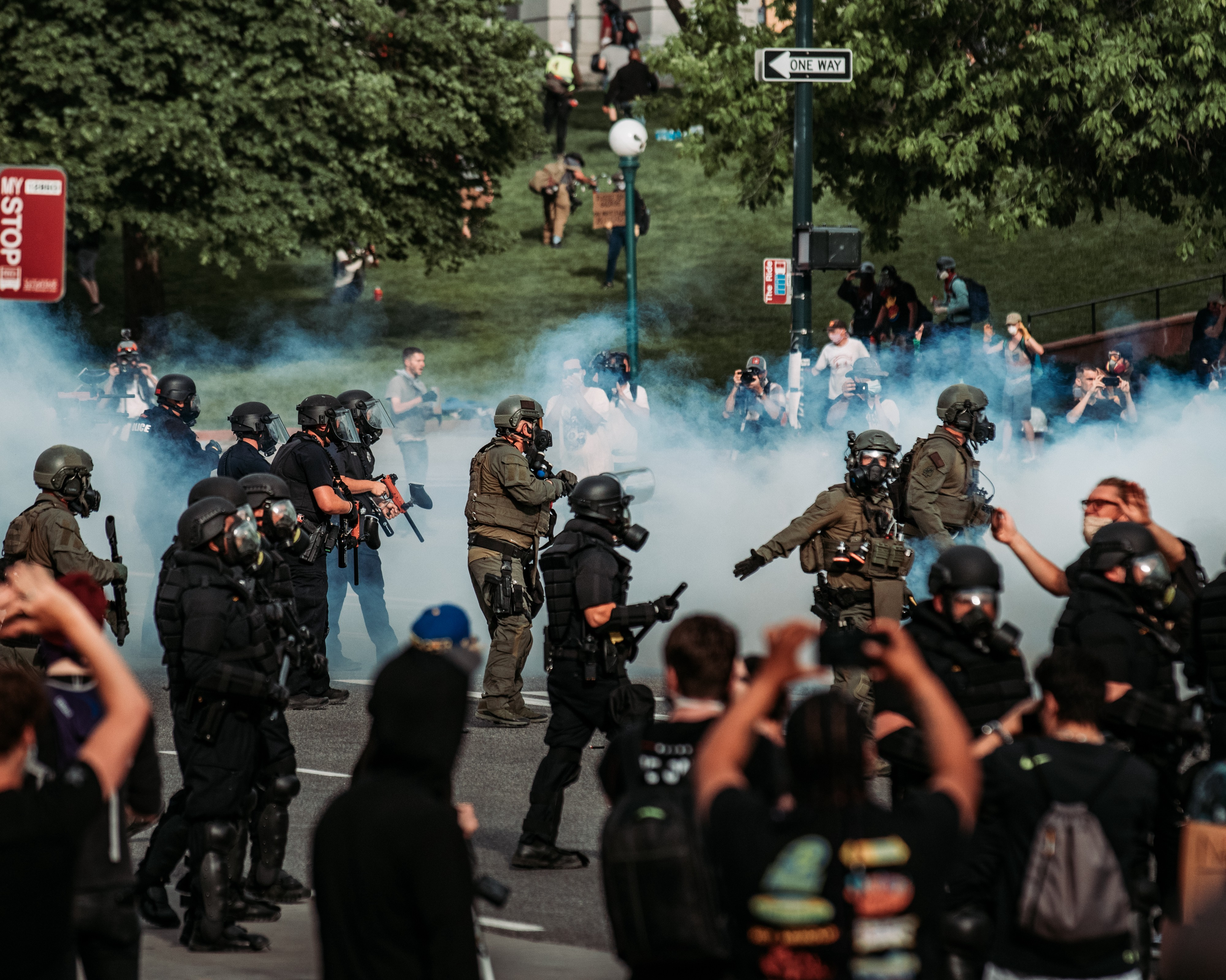 Image of riot police in a crowd with smoke bombs