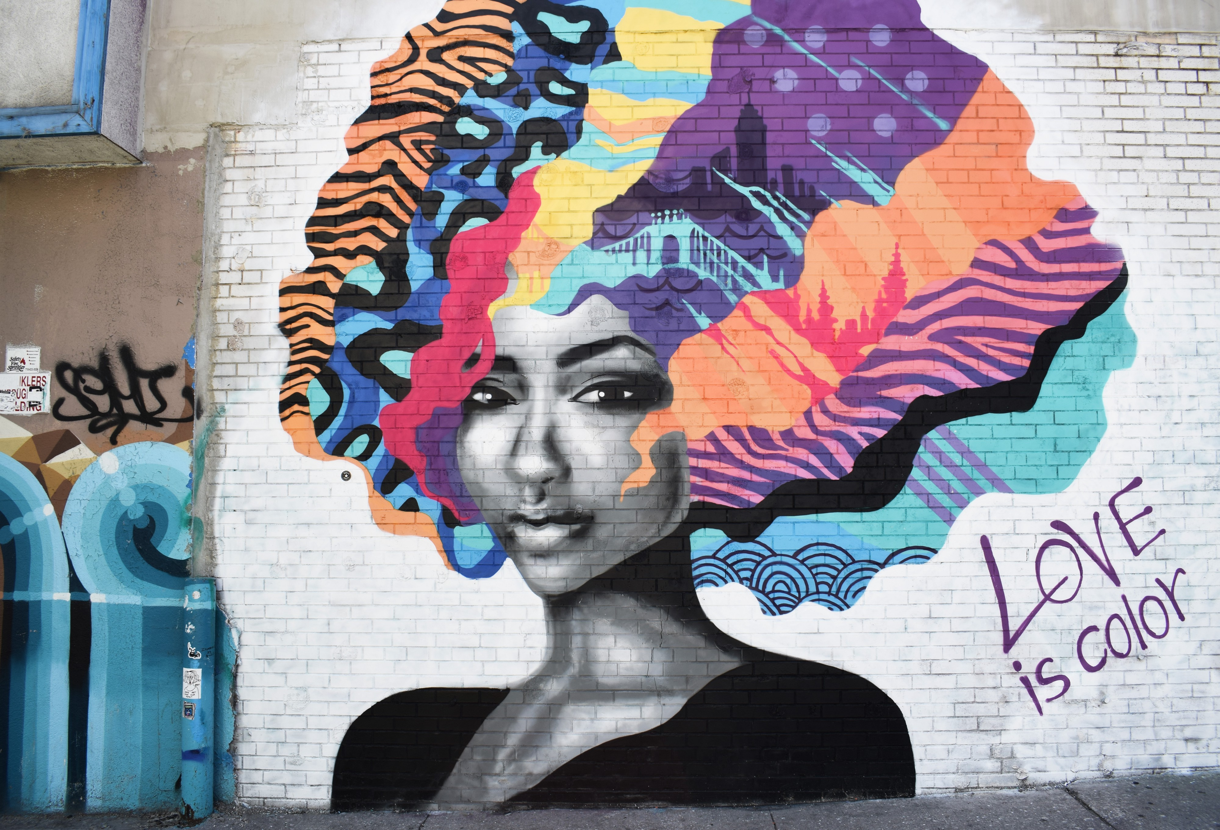"""A mural of a woman's face on a white brick wall with a colorful afro and the caption """"Love is color"""""""