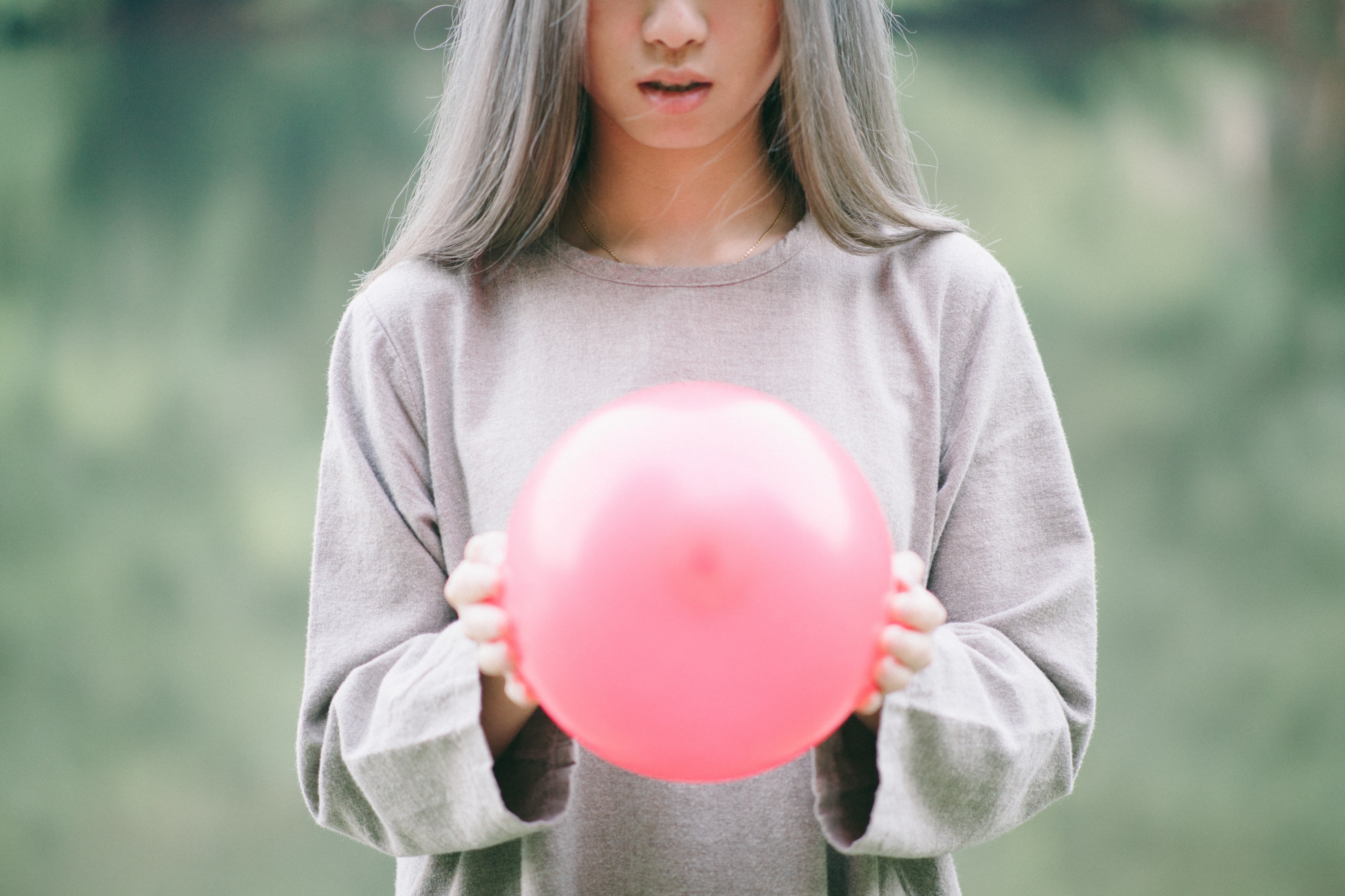 woman with long silver hair holding pink beach ball