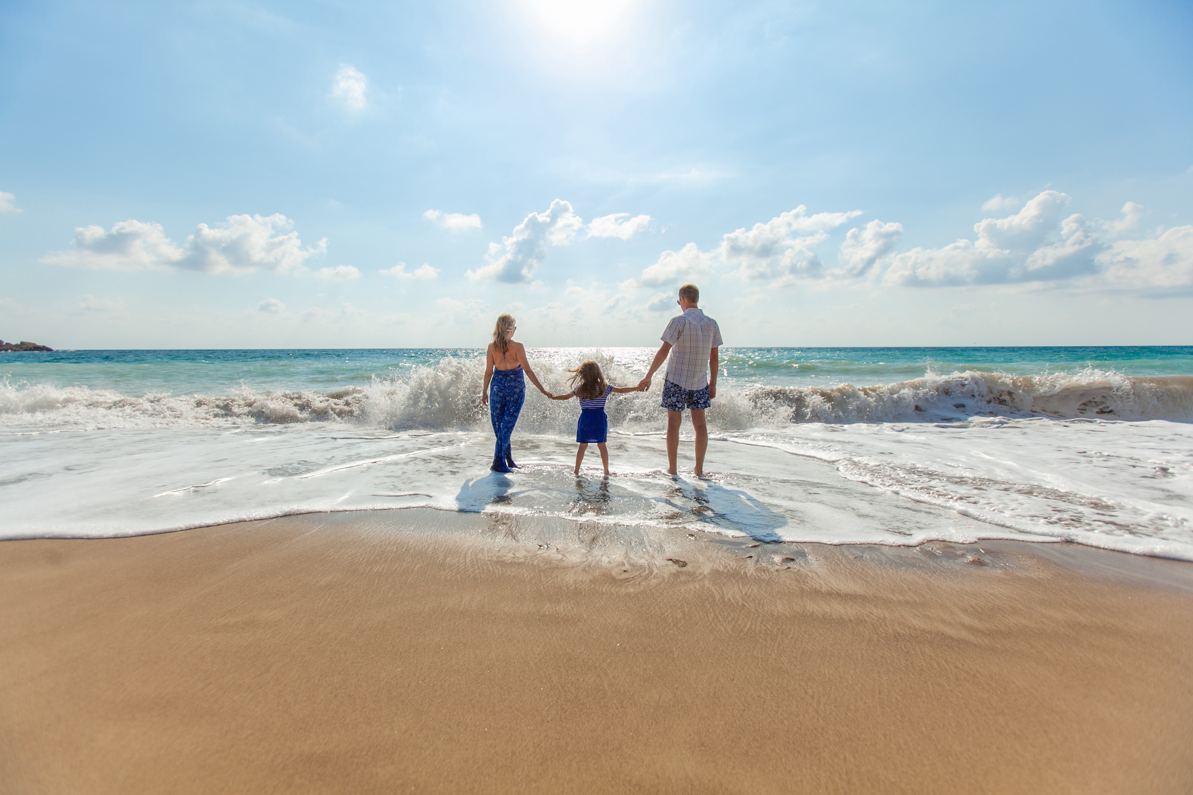 A family standing on a beach, enjoying themselves on a sunny afternoon.