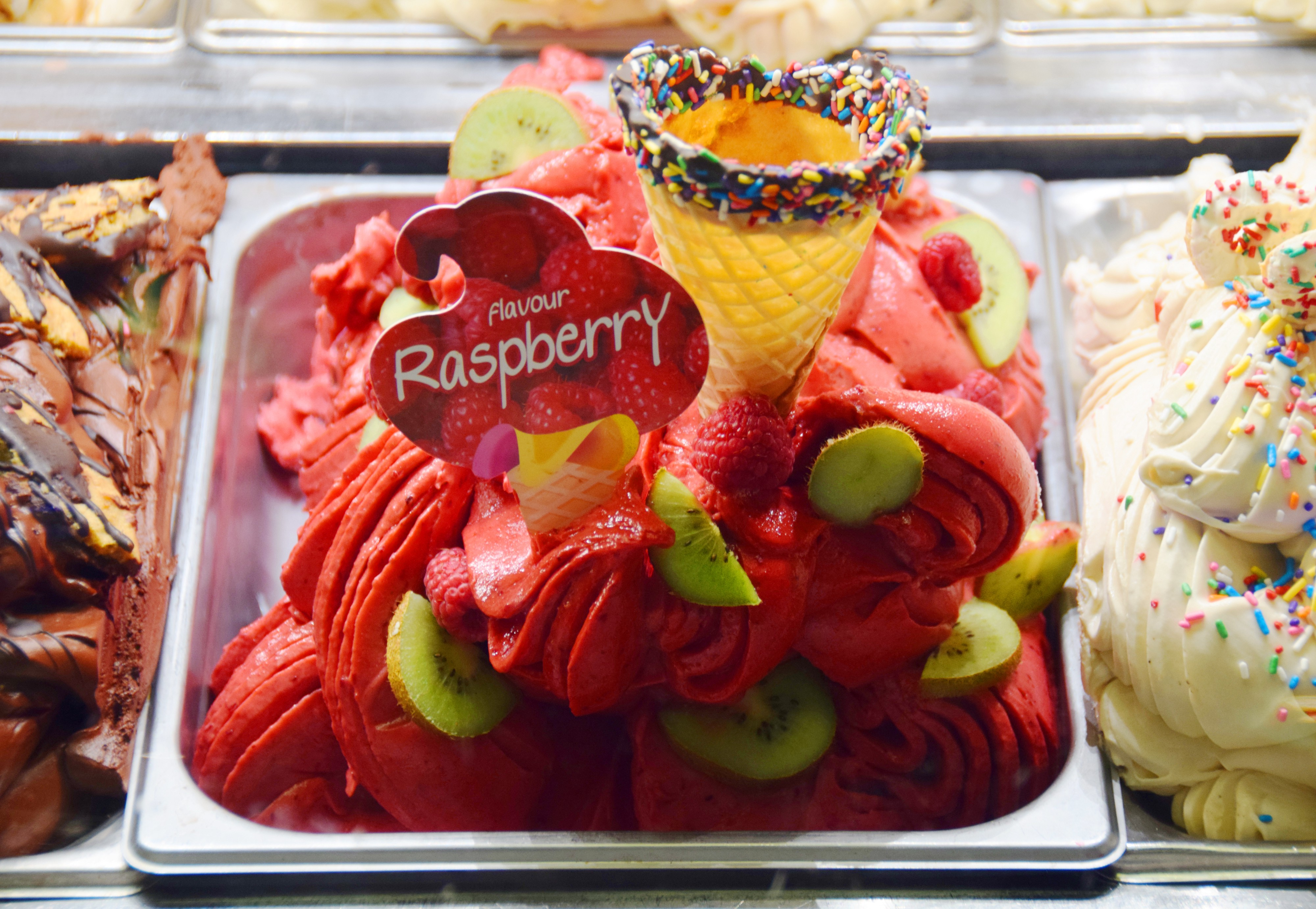 A dish of bright pink whipped raspberry sorbet with kiwi