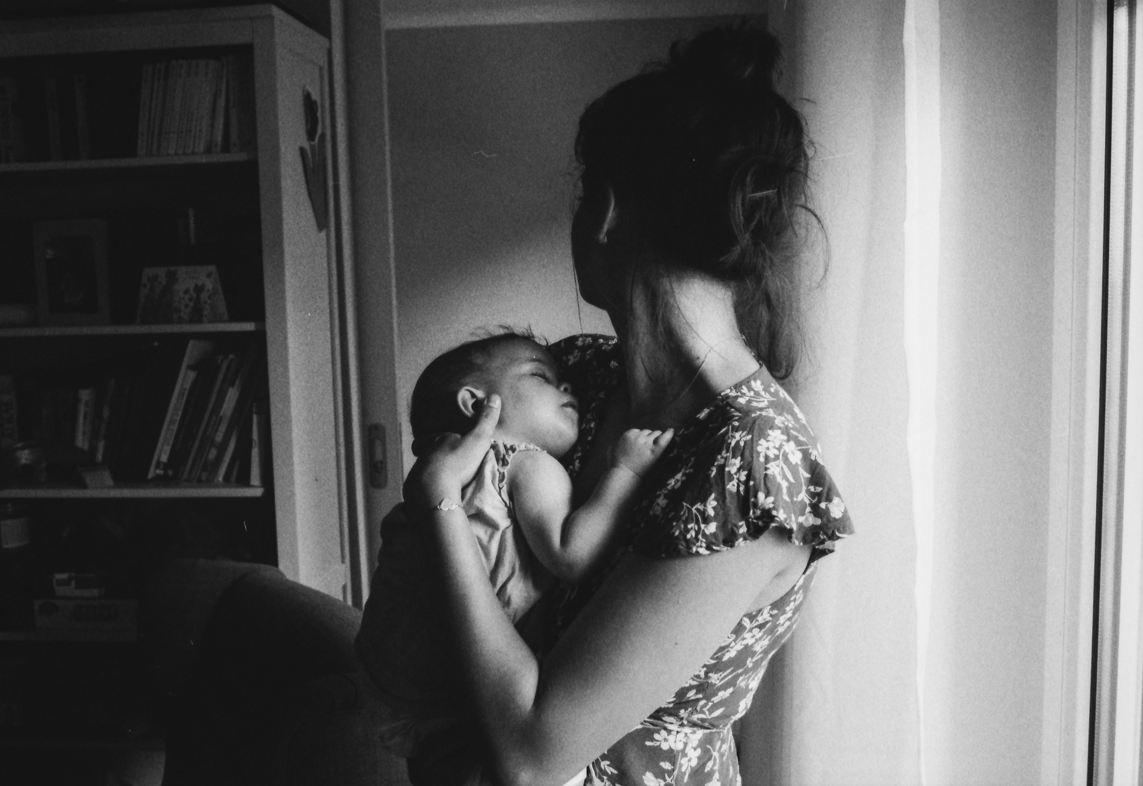 Black and white image of young mother holding her baby and looking sideways.