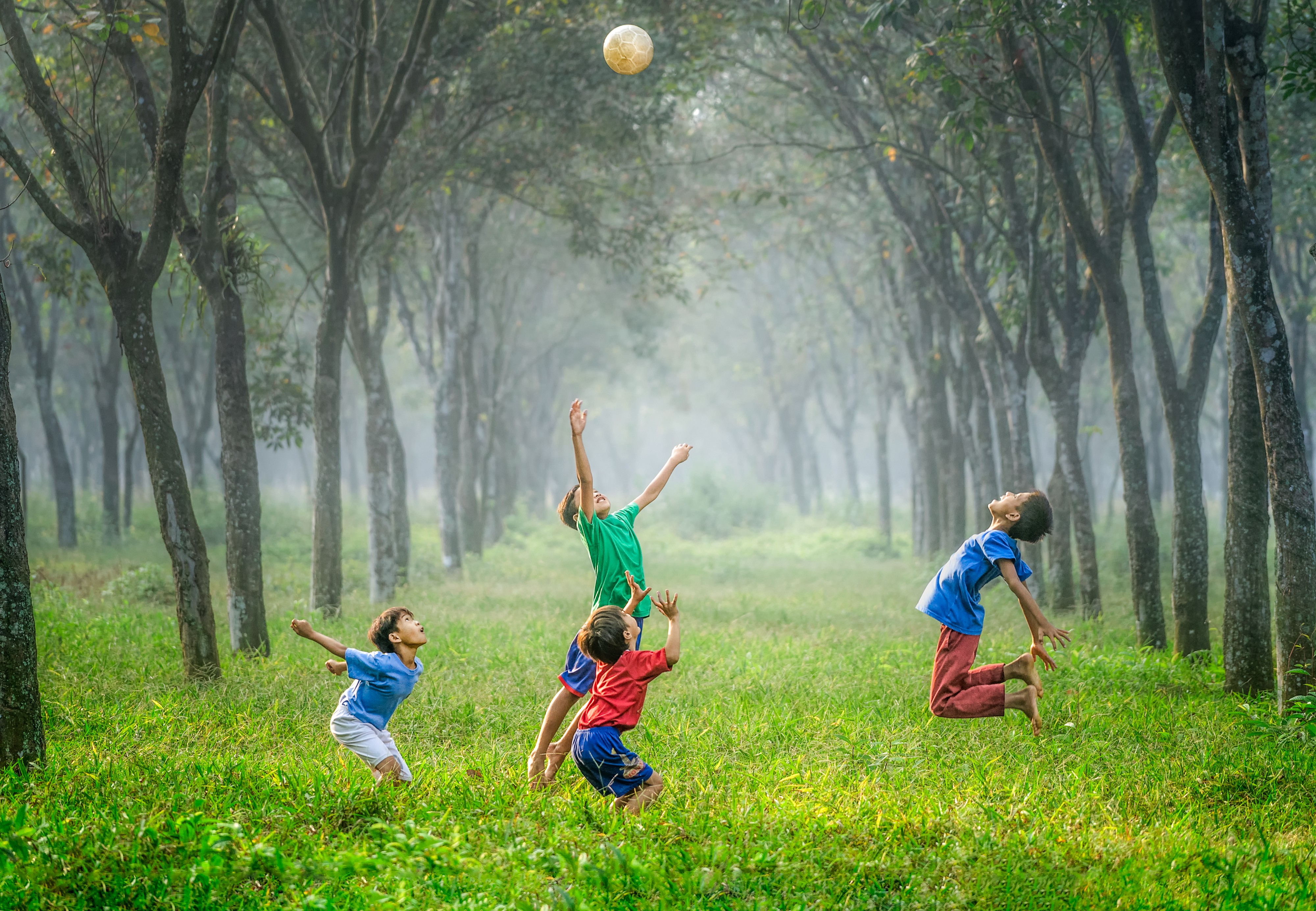 Children playing with a ball in an orchard. Relaxation is vital to health, doing something you find fun.