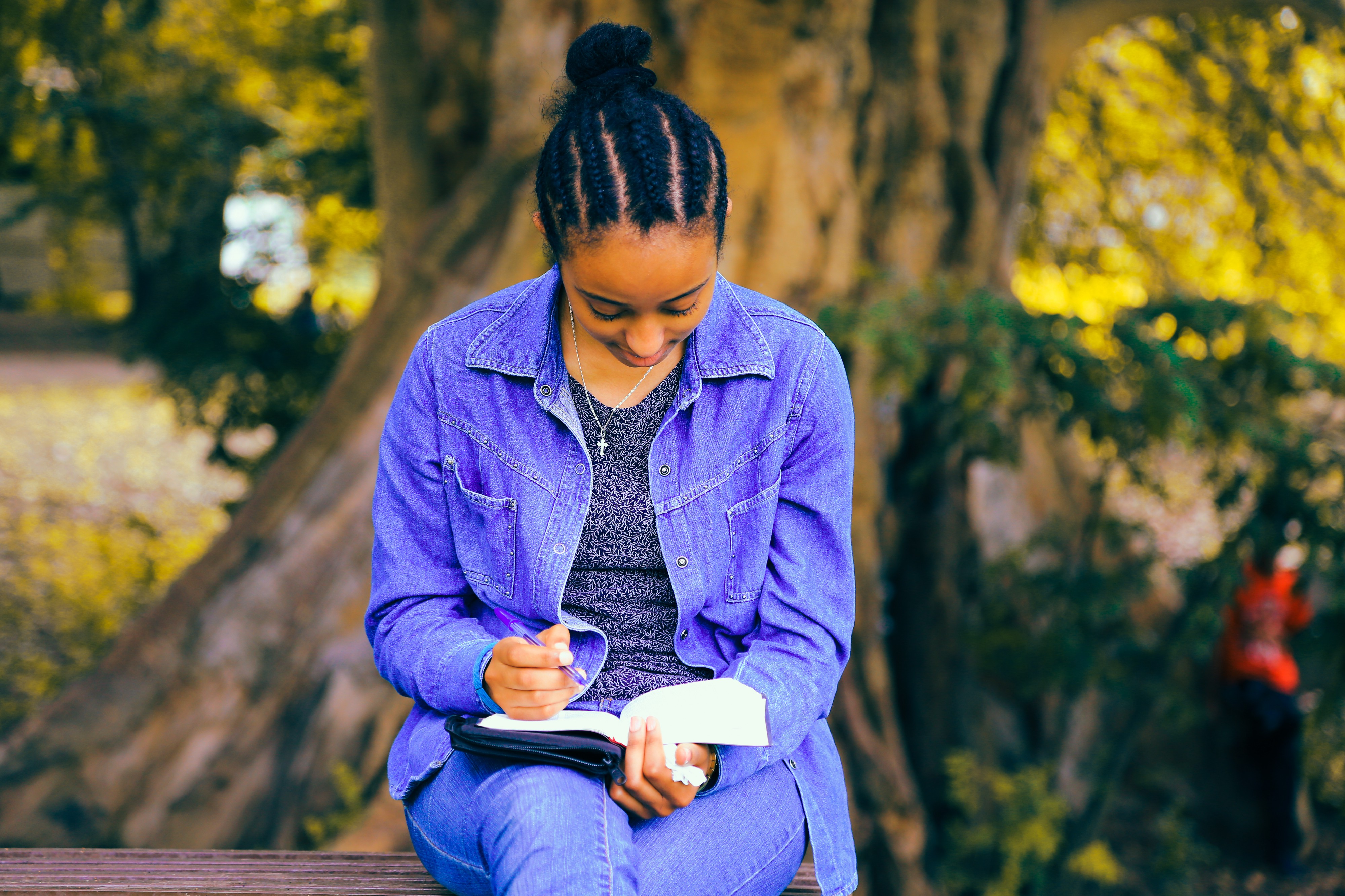 Woman sitting under a tree, smiling as she writes