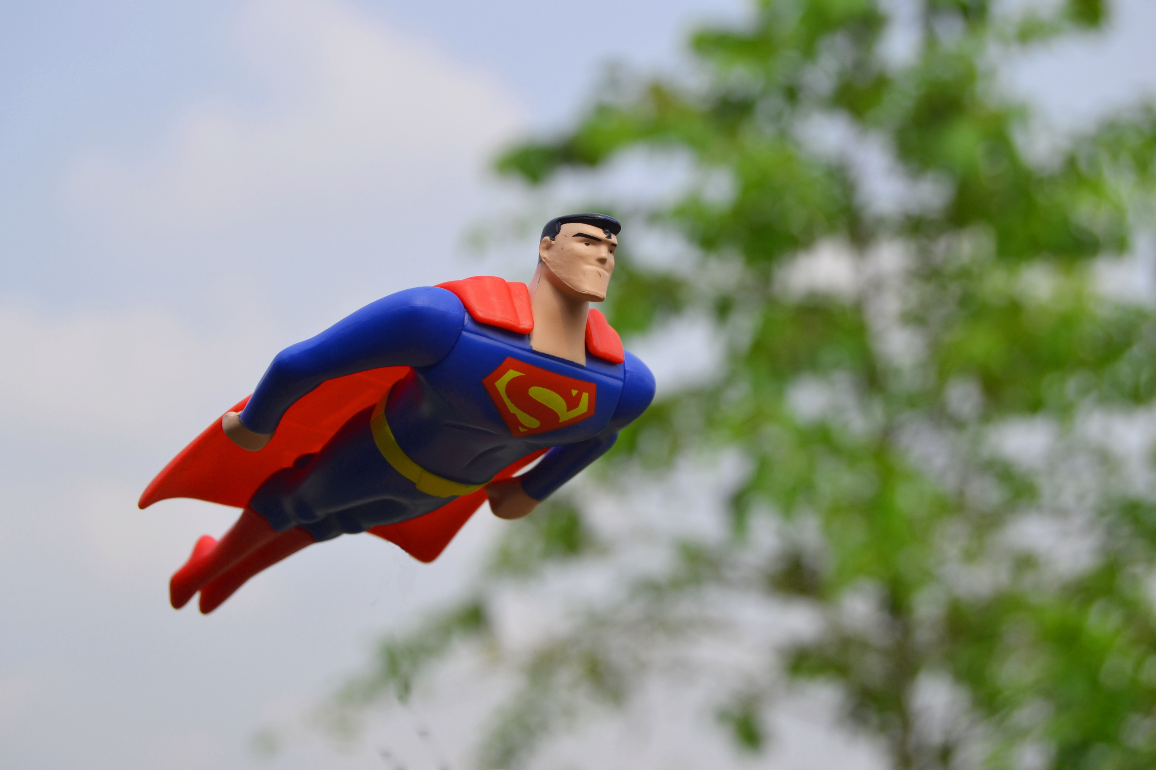 An action figure of Superman flies through the air in front of a green tree
