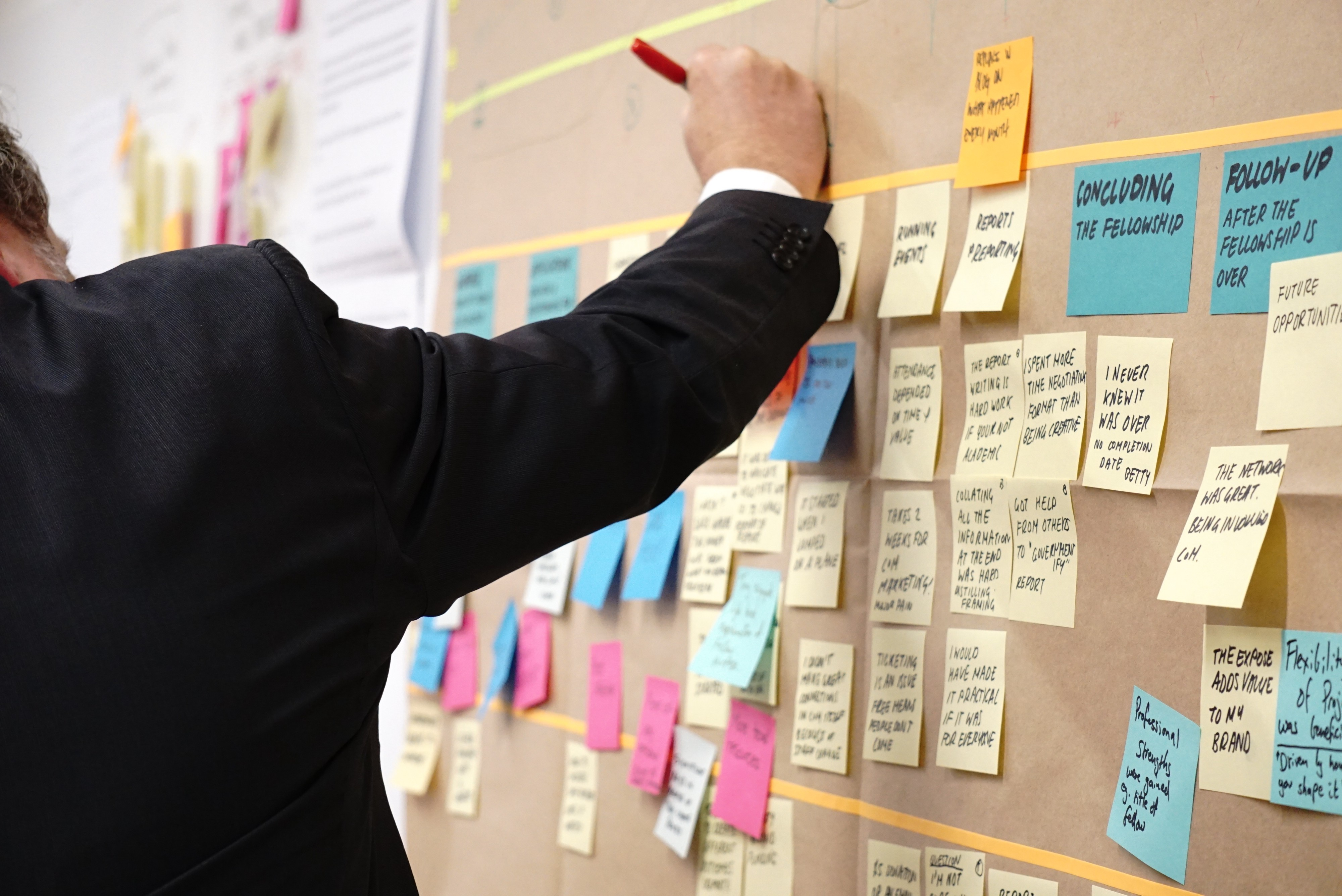 Man in a suit writes something down on a board with a bunch of sticky notes