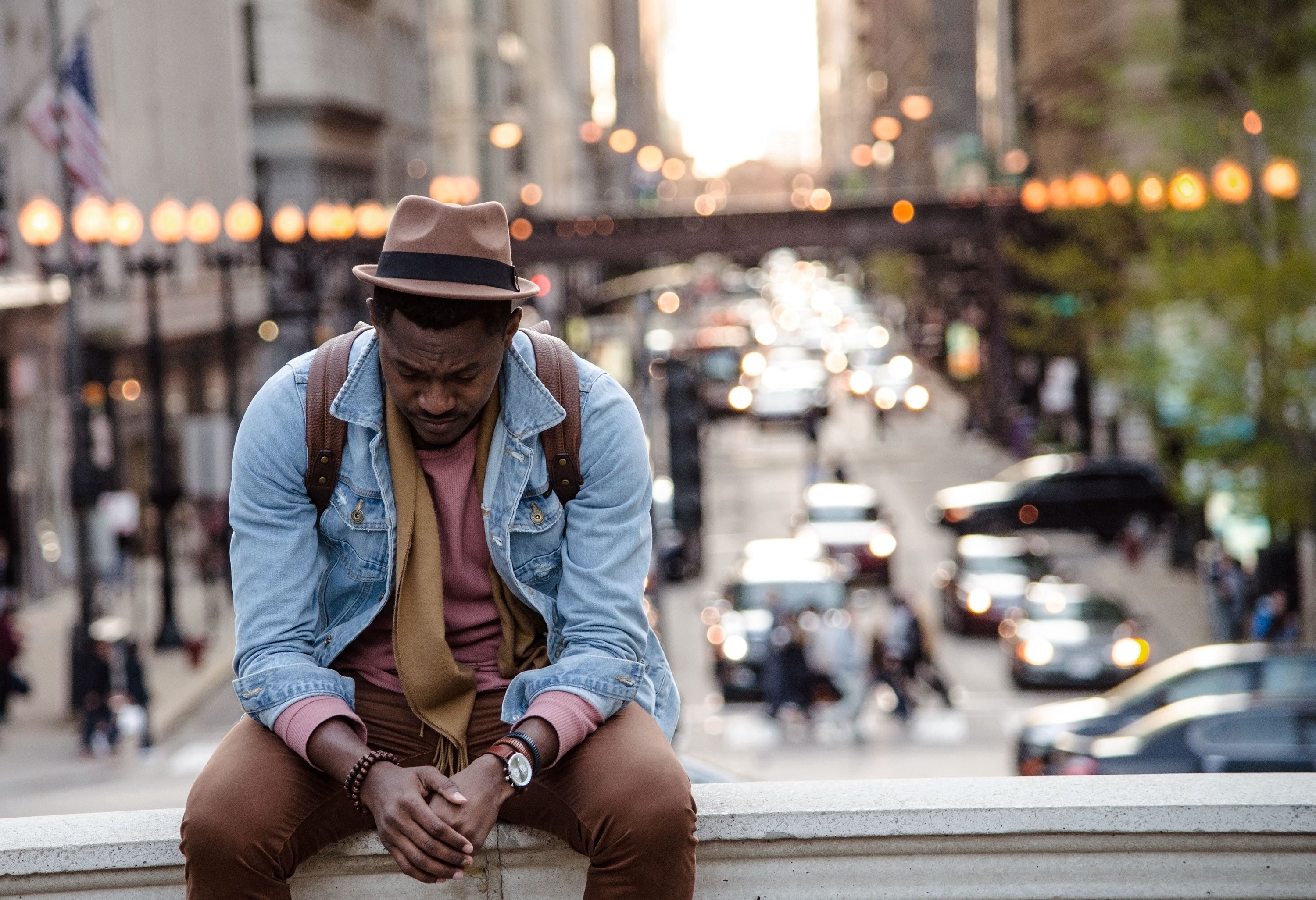 african-american man sitting on wall ledge with street fair in background