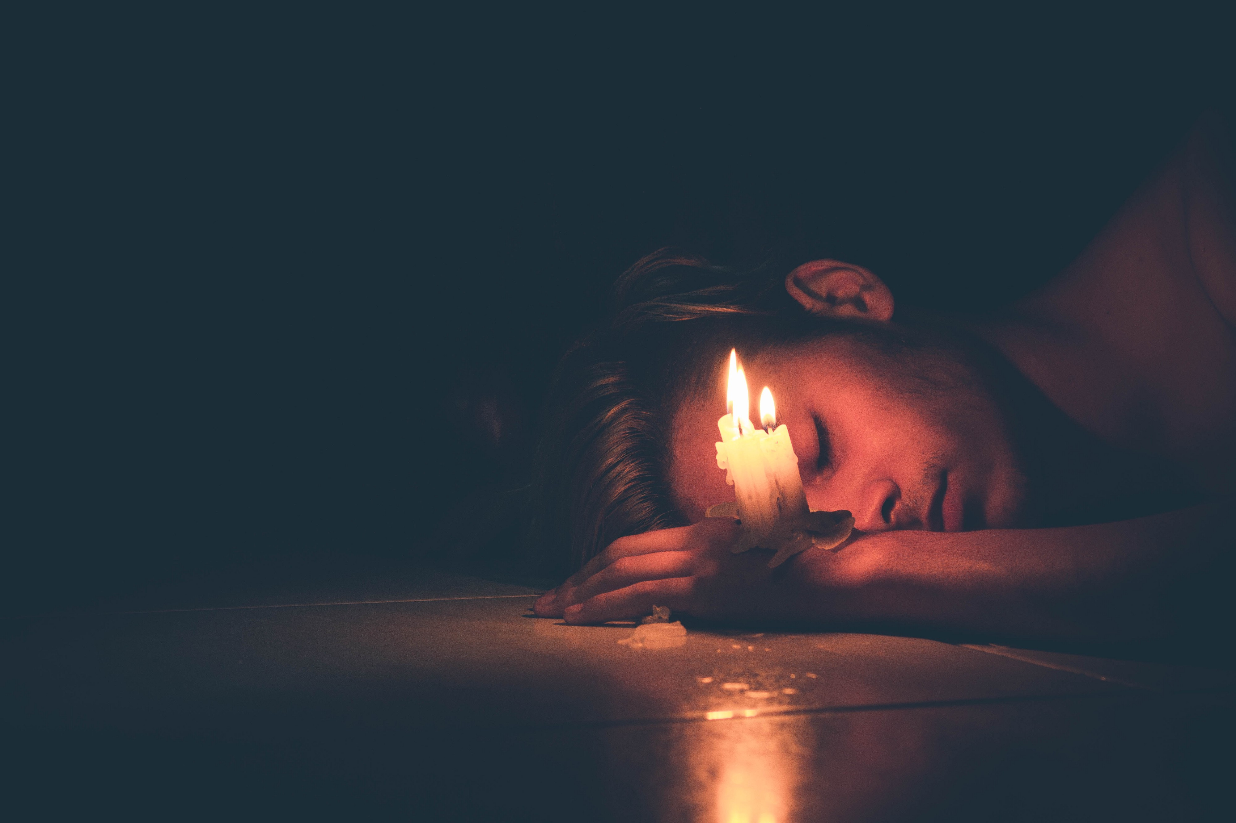 A sleeping woman holds a burning candle