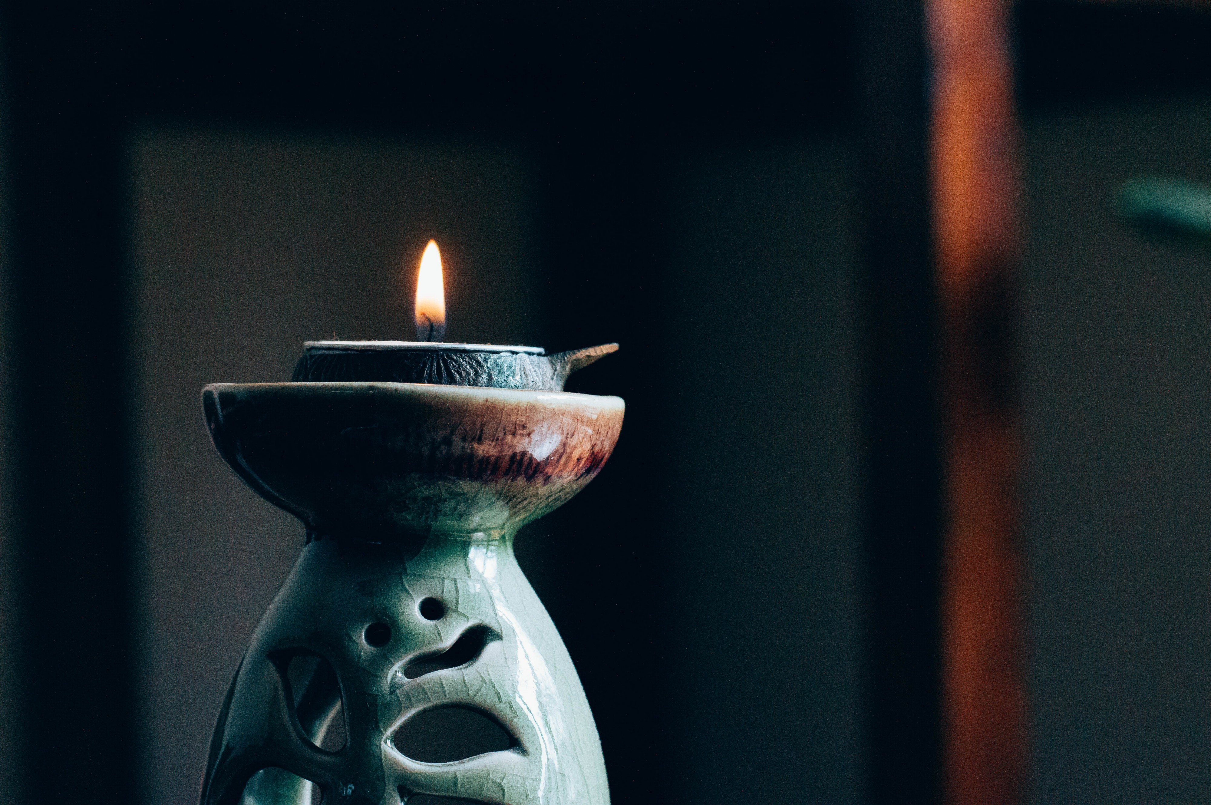 lit candle in a small ceramic bowl on top of a beautiful greenish grey art sculpture with engravings of birds and leaves and circles.