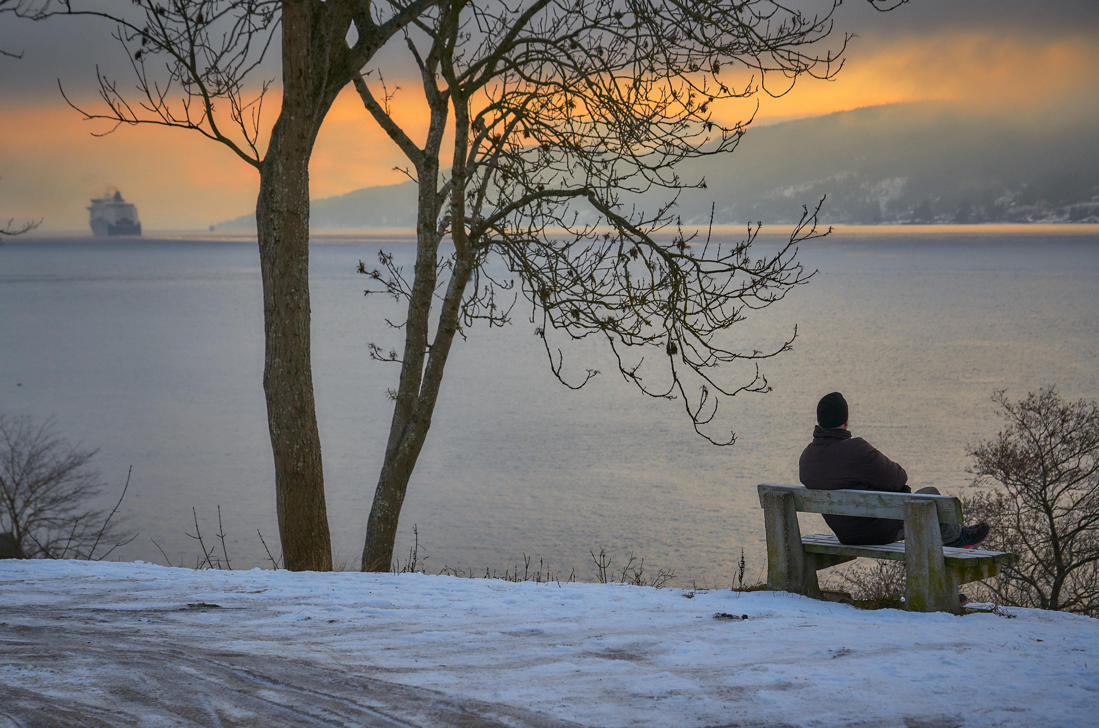 A person contemplating life sitting by a large lake