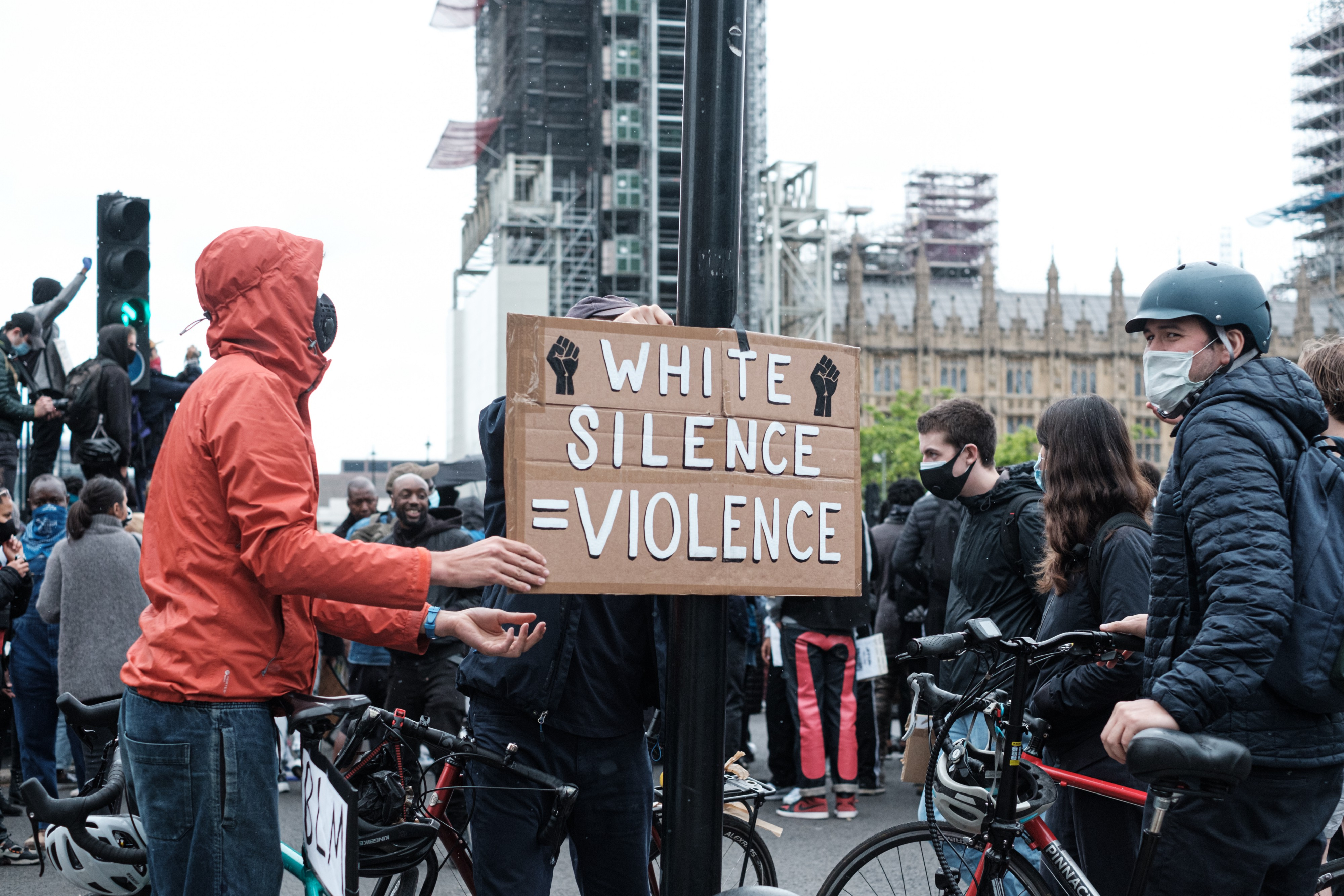 "A masked white man holds a cardboard sign while white onlookers watch. The sign says ""White Silence Equals Violence."""