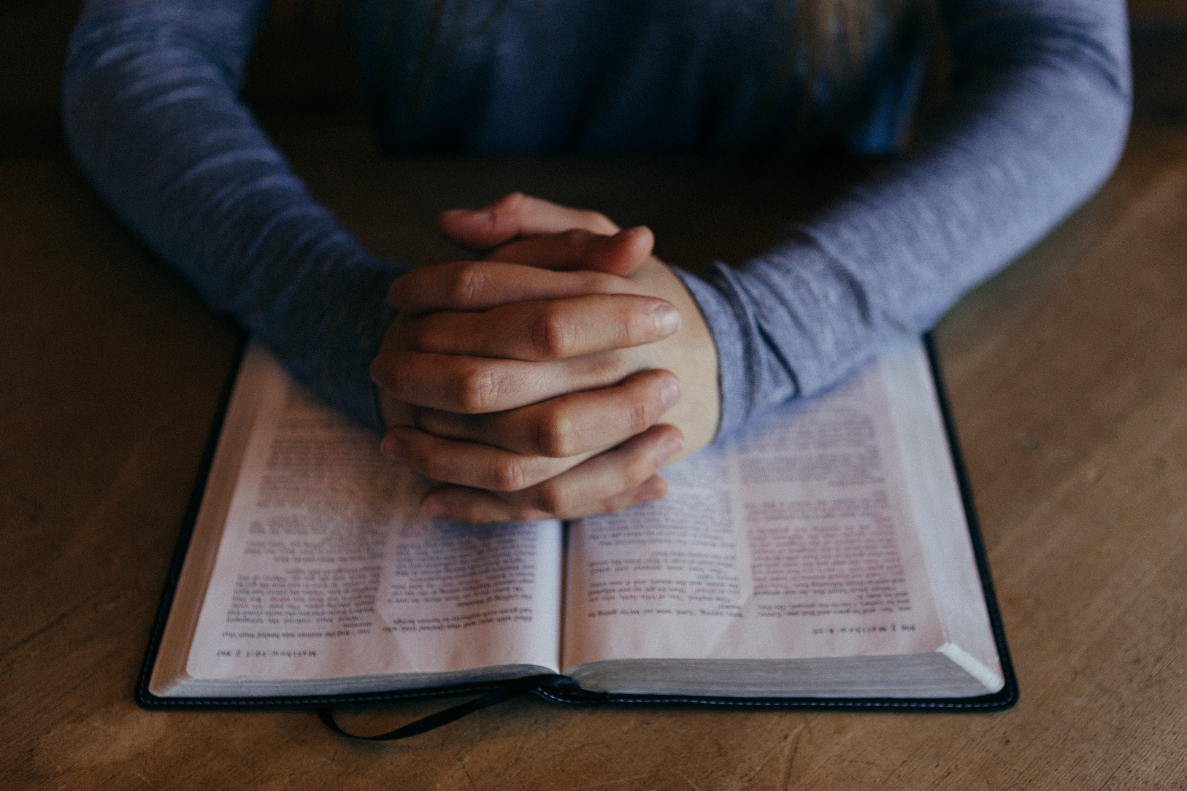 A pair of hands in a prayer position on an open bible