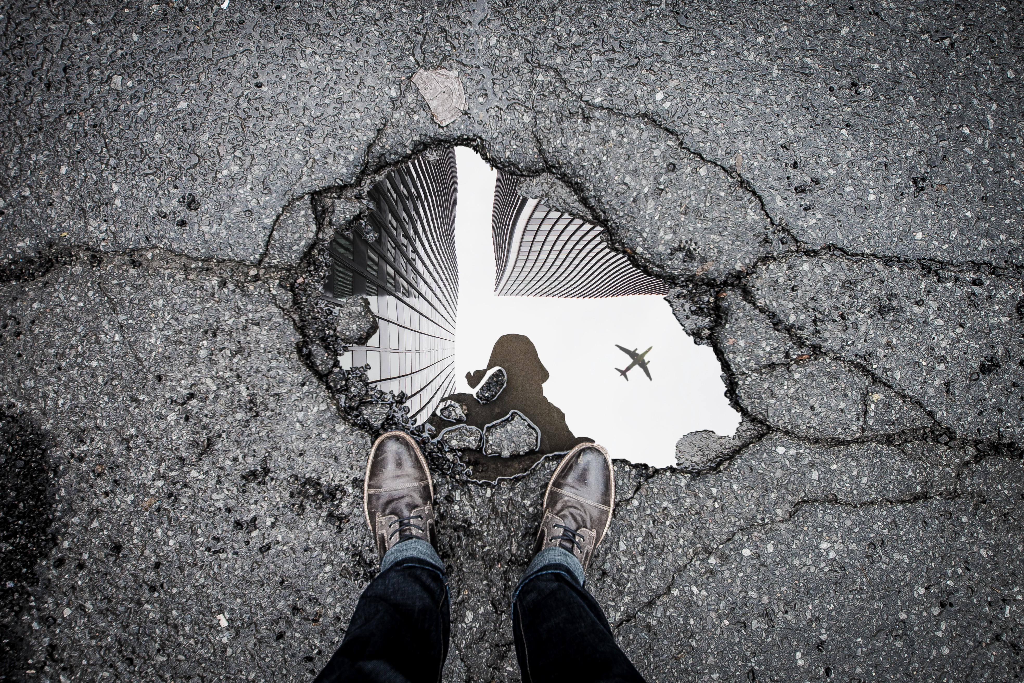 A photo of a puddle with the photographer, tall buildings, and a plane reflected therein
