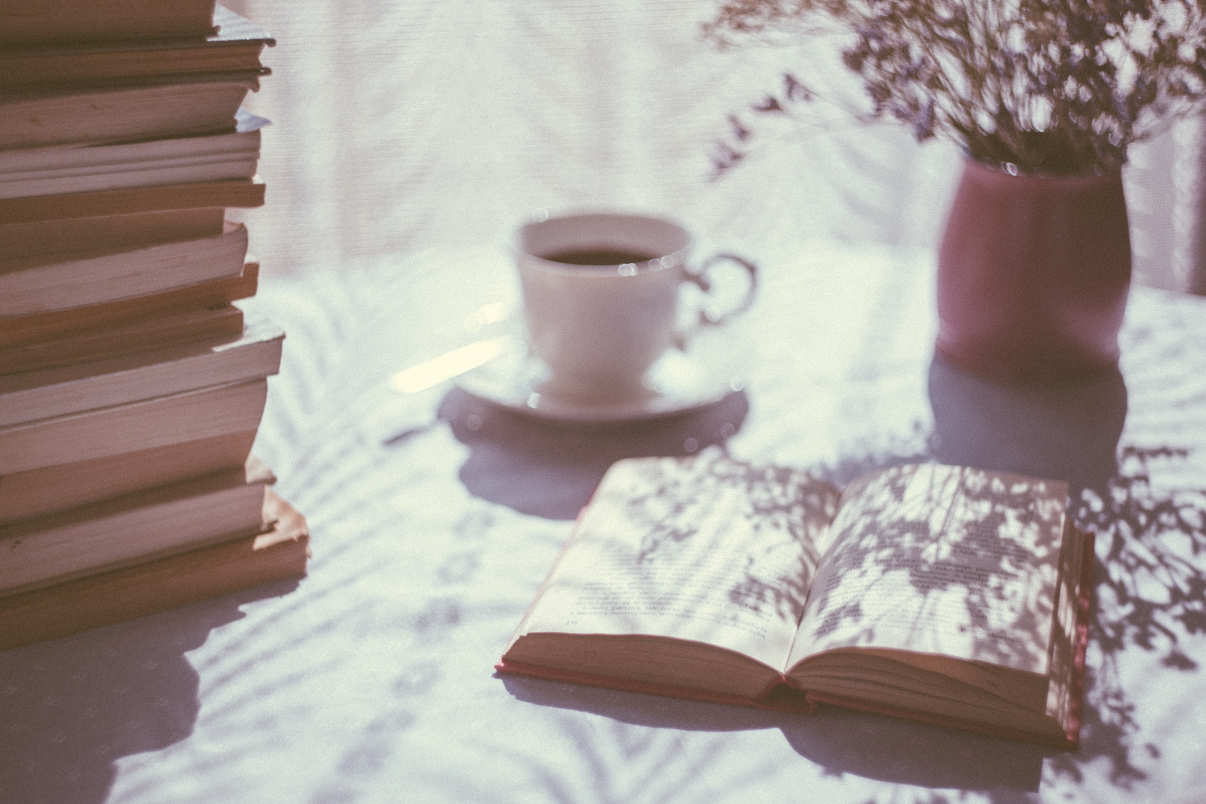 A pile of books sit on a table next to an open book and a cup of coffee. A vase with flowers sits at the back of the table, in front of white lace curtains.