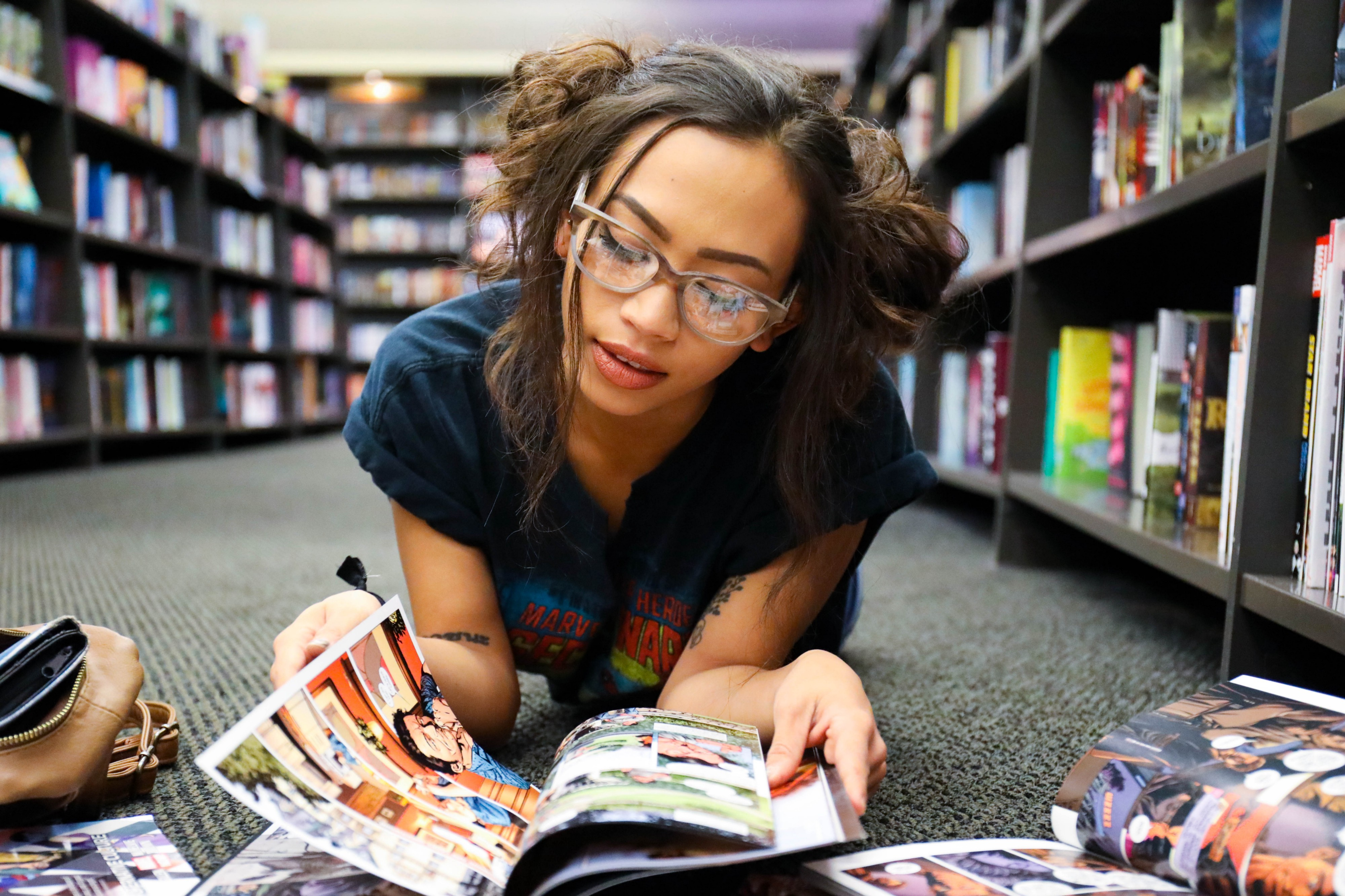 A young woman on the floor of a bookstore, paging through a comic book. She seems cool.