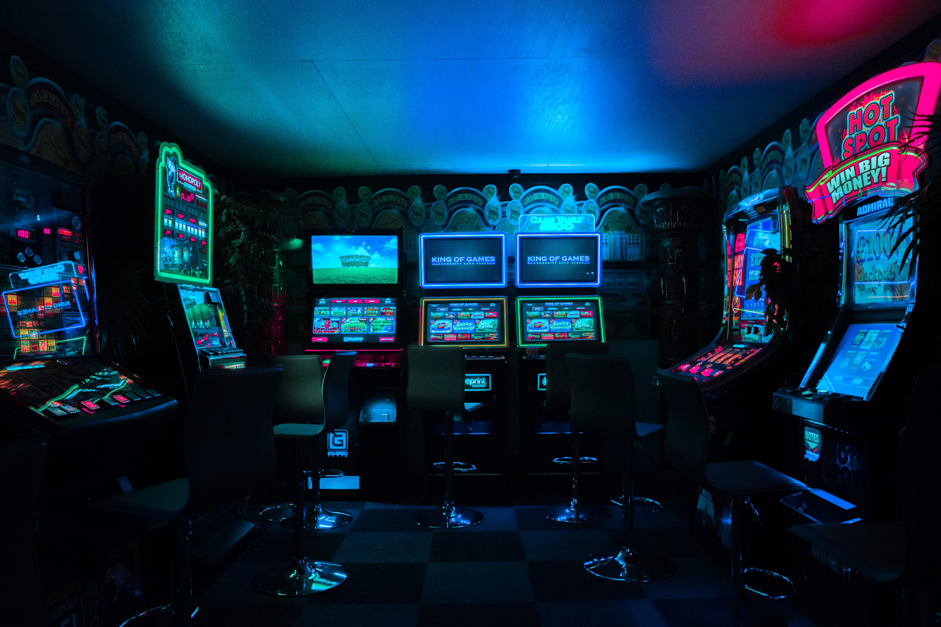 A photo inside an arcade with over-saturated neon lights behind the machines