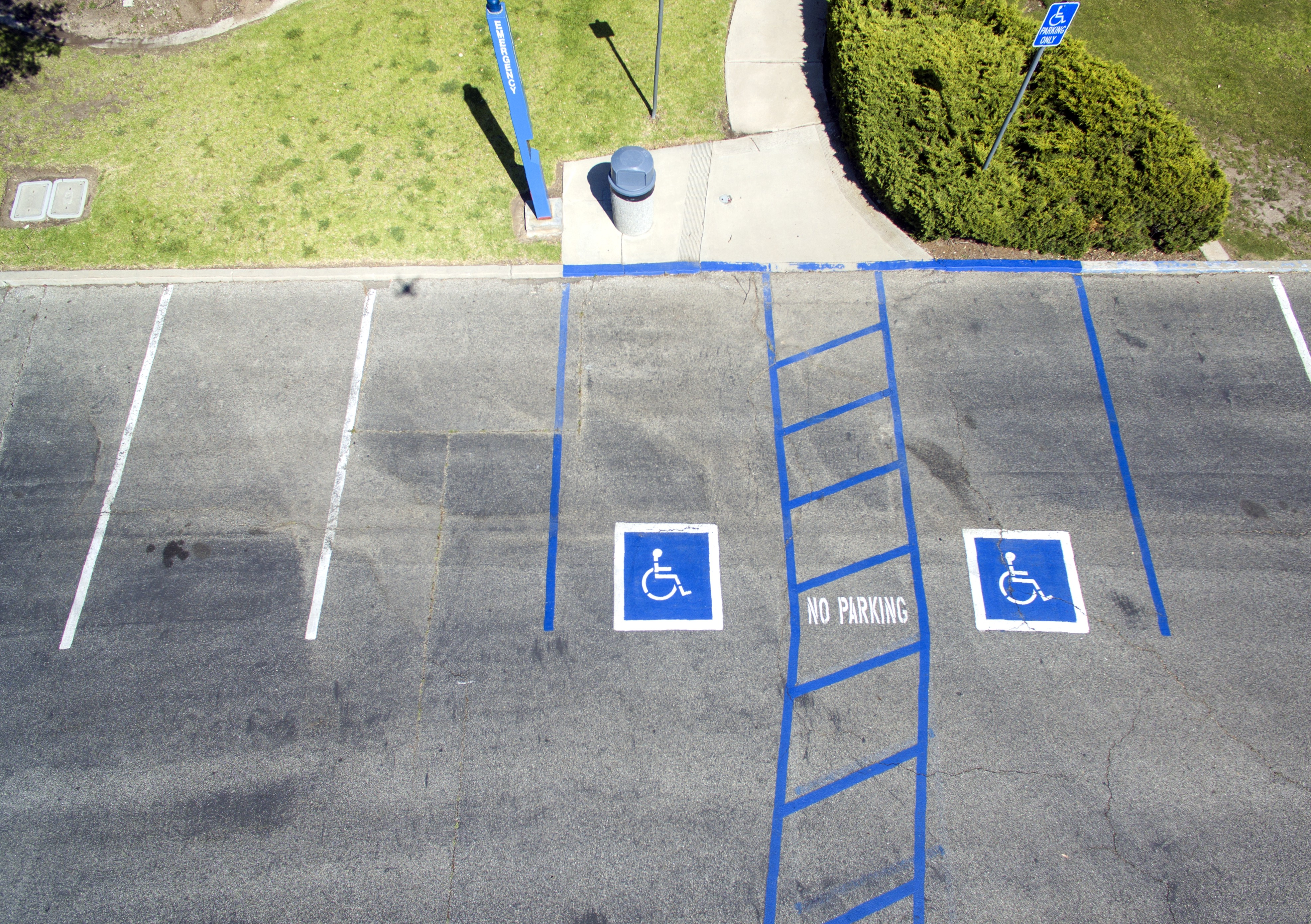 A zoomed-out image of two accessible parking spaces side-by-side, sharing an accessible aisle. The parking lot is grey, and the accessible parking spaces are painted in bright blue paint.