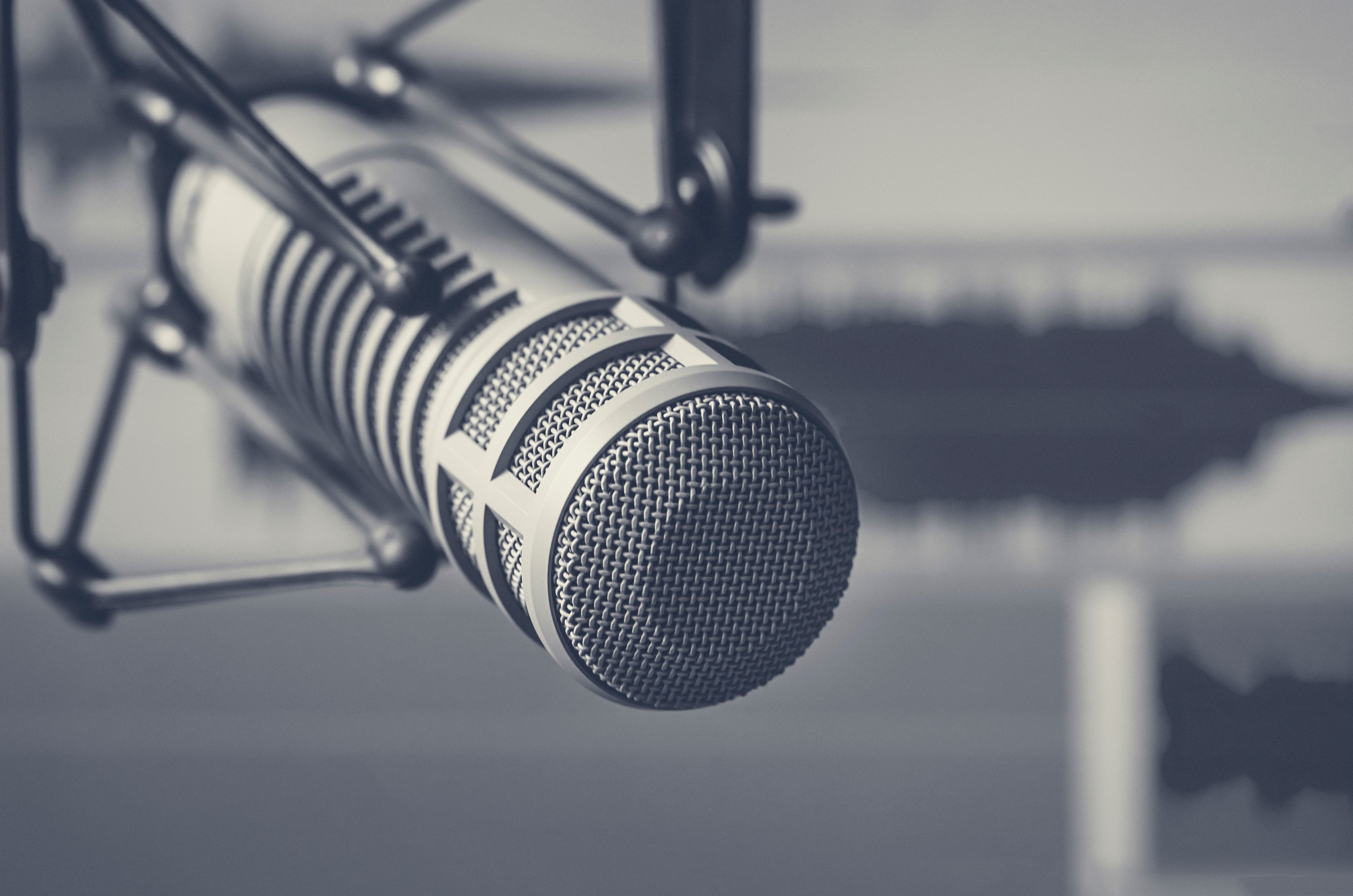 Close up of a professional microphone and sound wave form in the background.