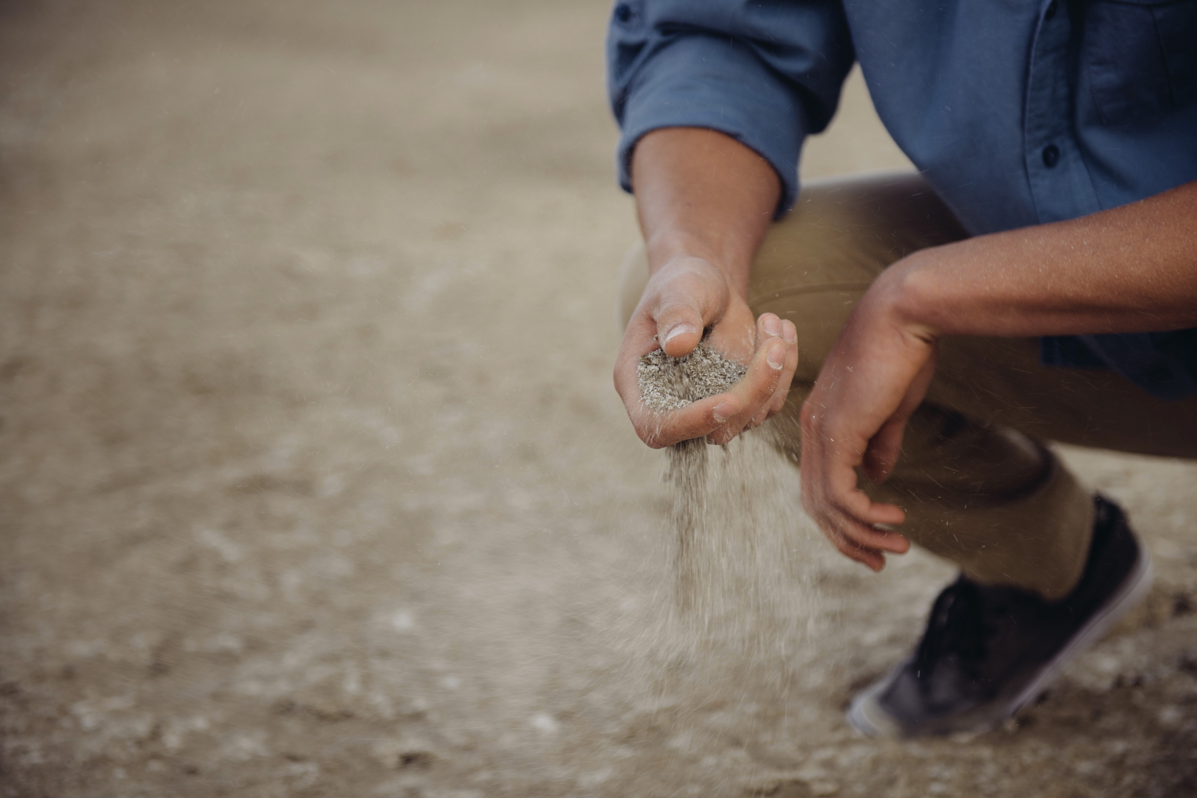A person sifts through dry soil
