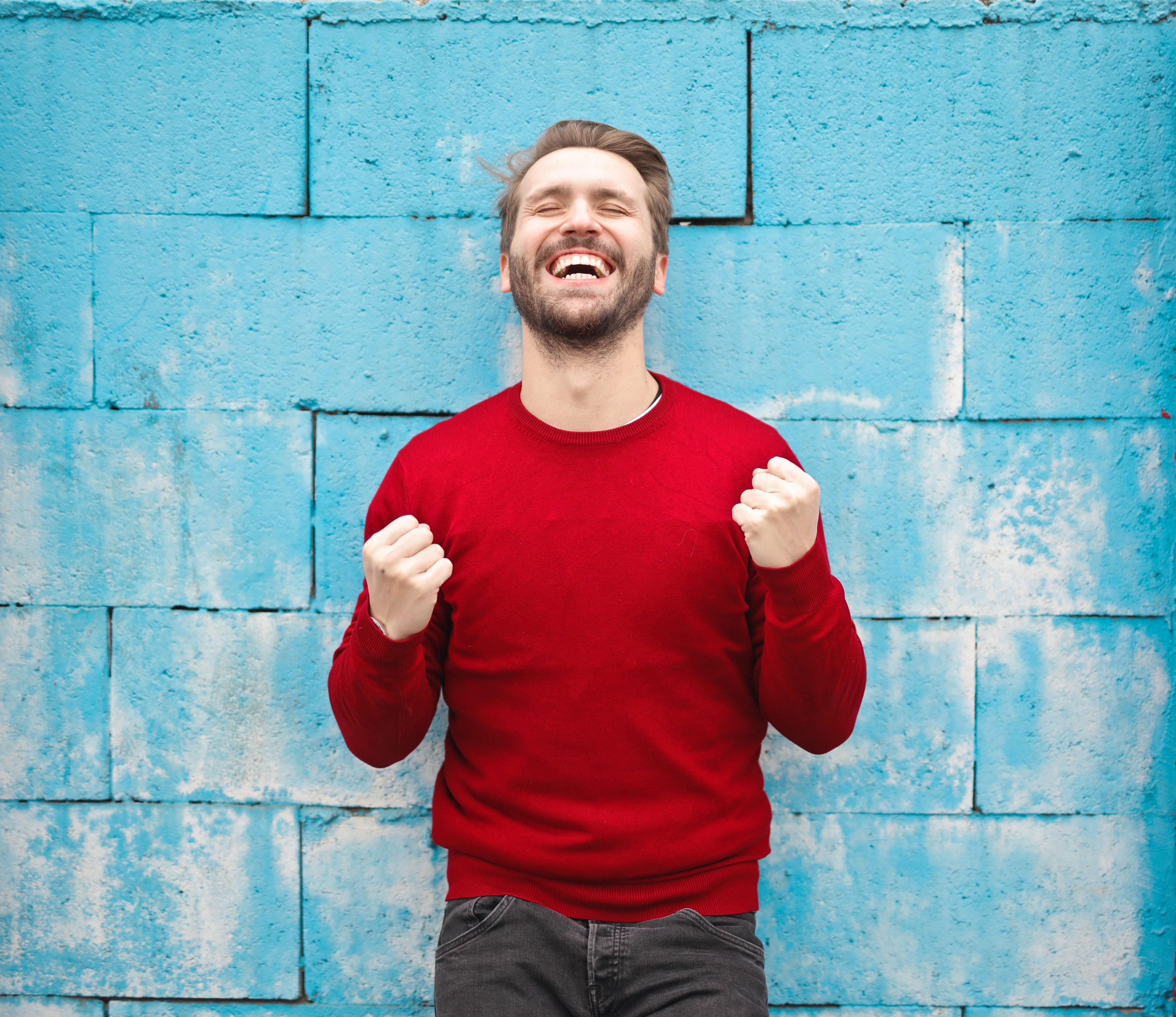 A excited man in a red sweater with his fists in the air in from of a blue brick wall.