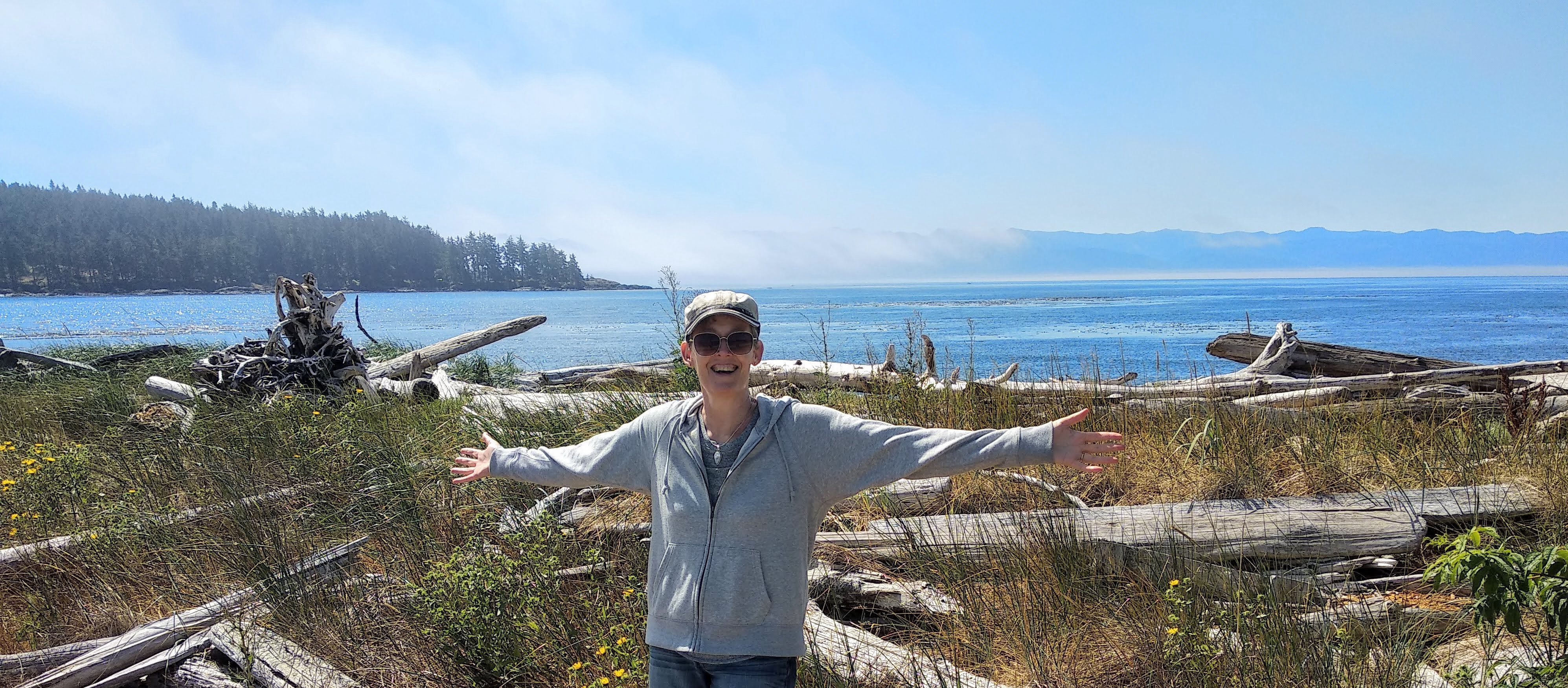 Author, Gill McCulloch on the beach in Sooke, BC, Canada against a background of blue sky, ocean and trees. In the foreground are driftwood logs and shrubs.