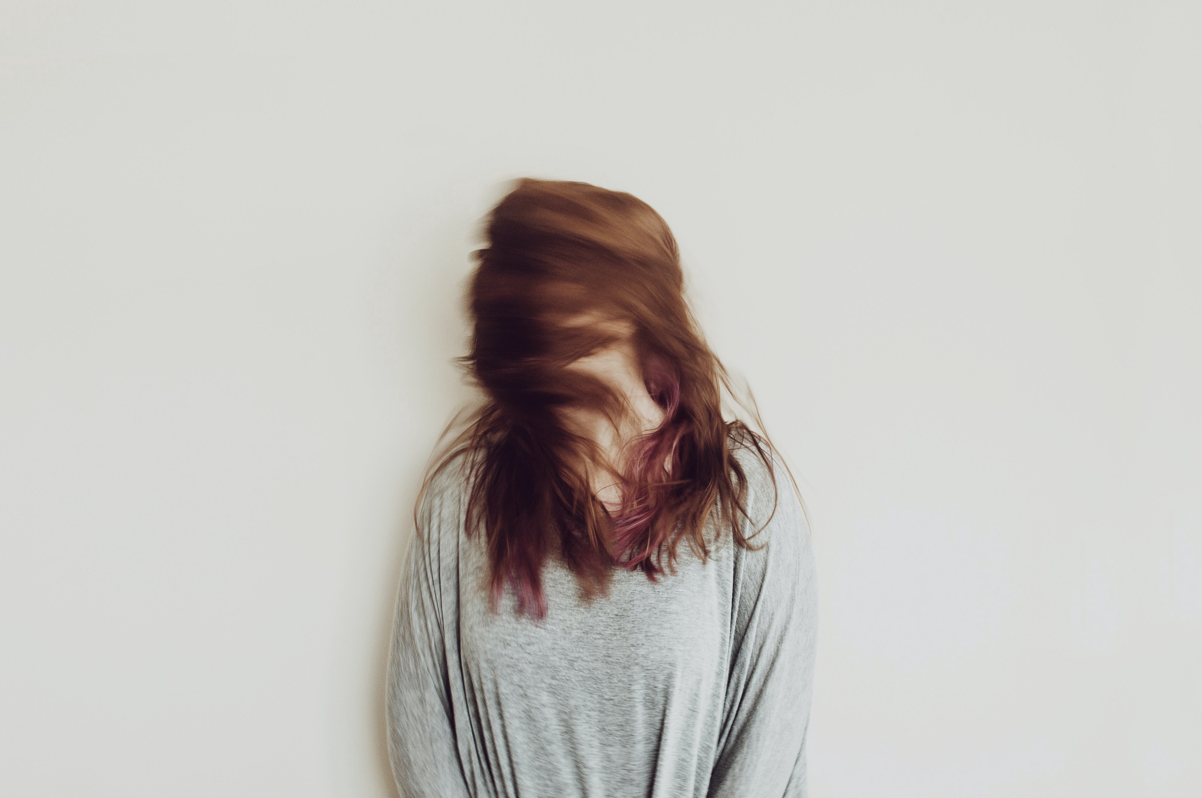 Woman with her head turned to the side, her face obscured by her blowing hair