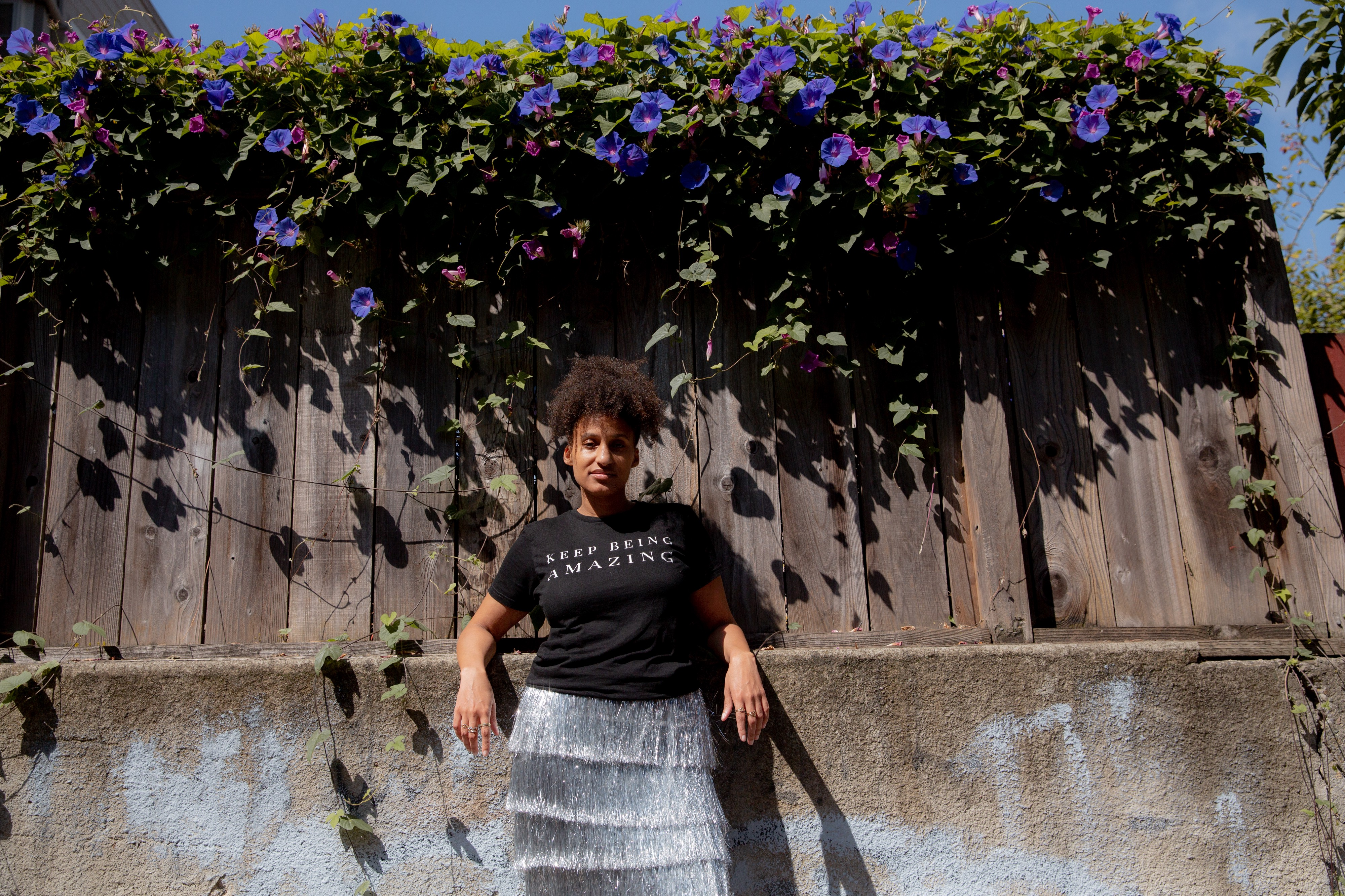 Akilah Cadet leaning backwards on her elbows against a concrete retaining wall. A fence with flowering ivy is above her.