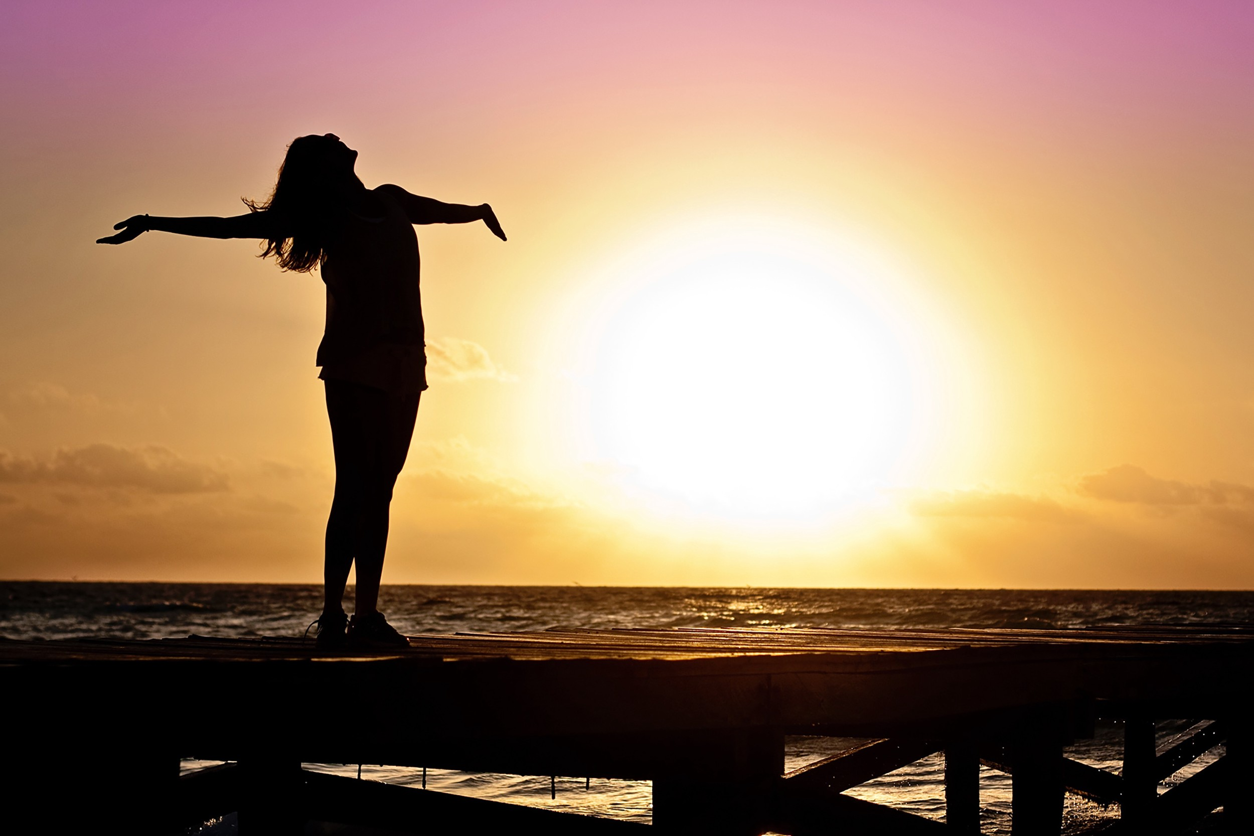 Woman by ocean with arms open wide conveying the feeling of freedom.