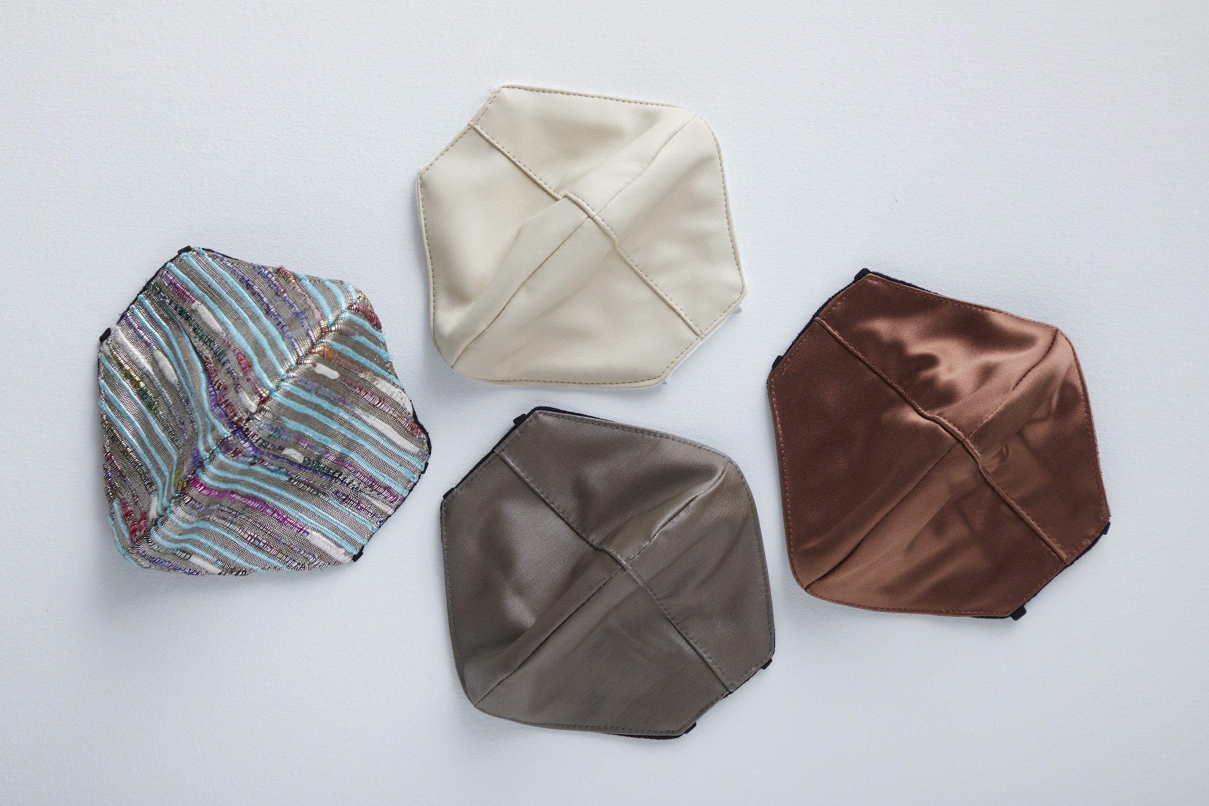 4 shimmery cloth facemasks. Three are solid-colored neutrals and one has sequined blue, purple, and gray stripes.