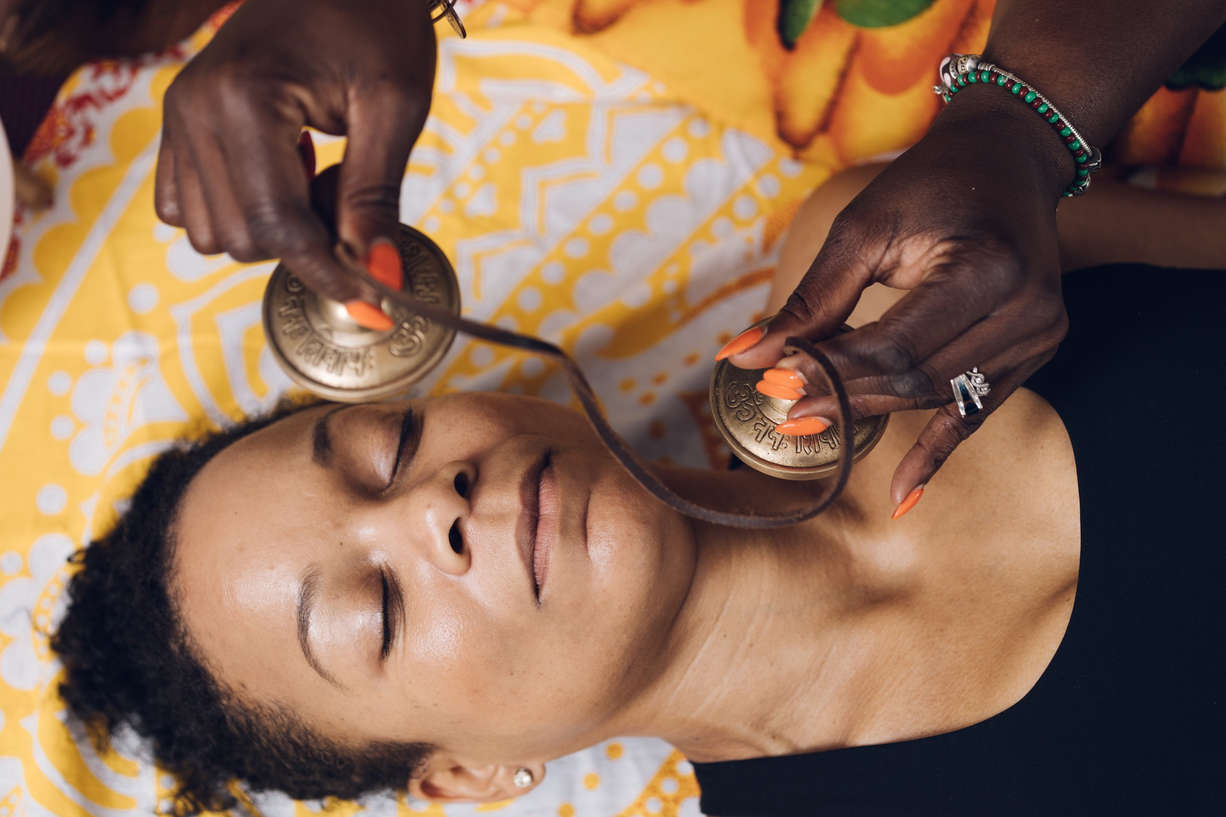 A holistic practitioner holding bells over the face and neck of a person lying on their back with their eyes closed.