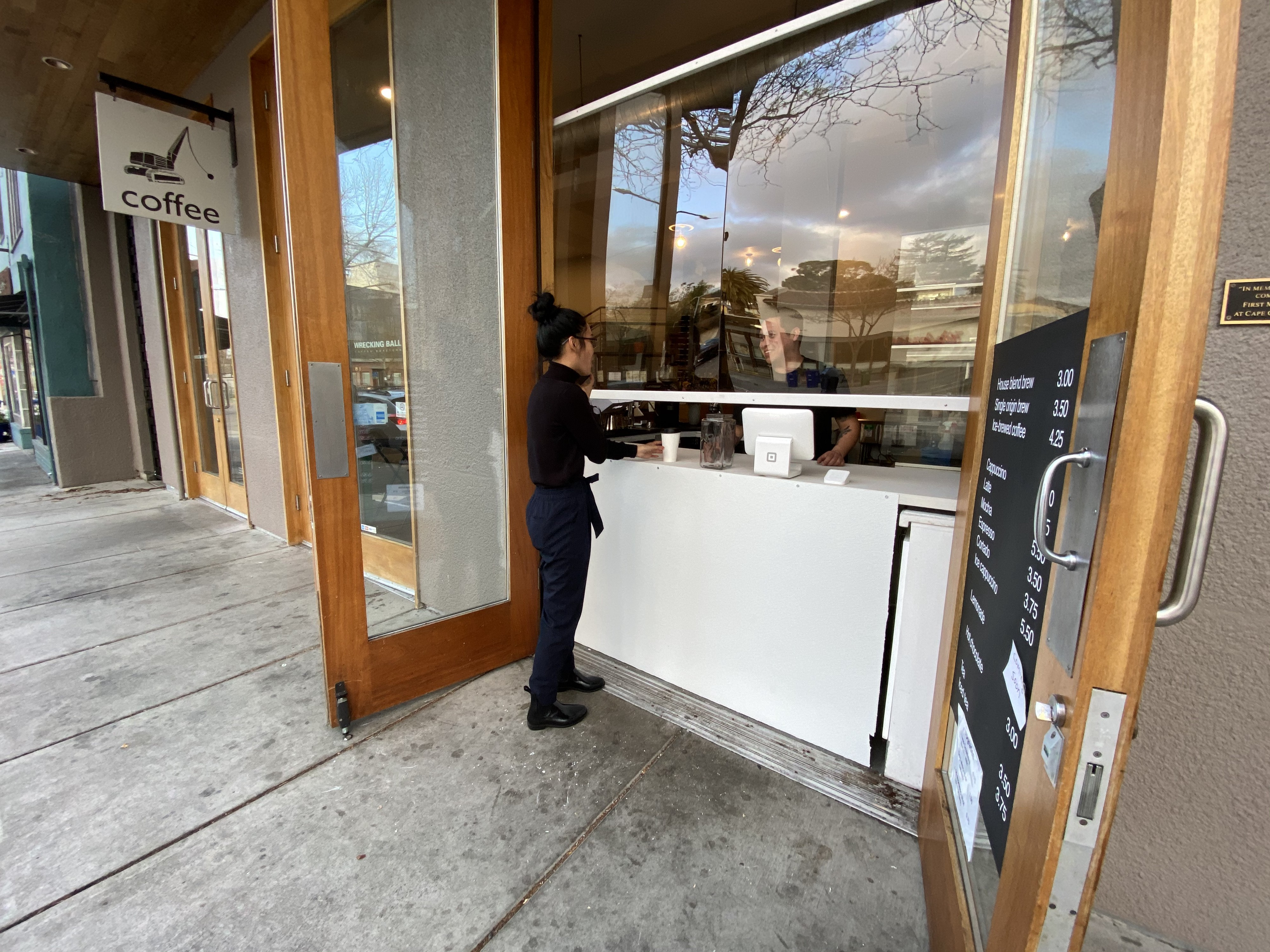 Open double-doors reveals a white counter and glass partition as a person is served coffee from a barista.