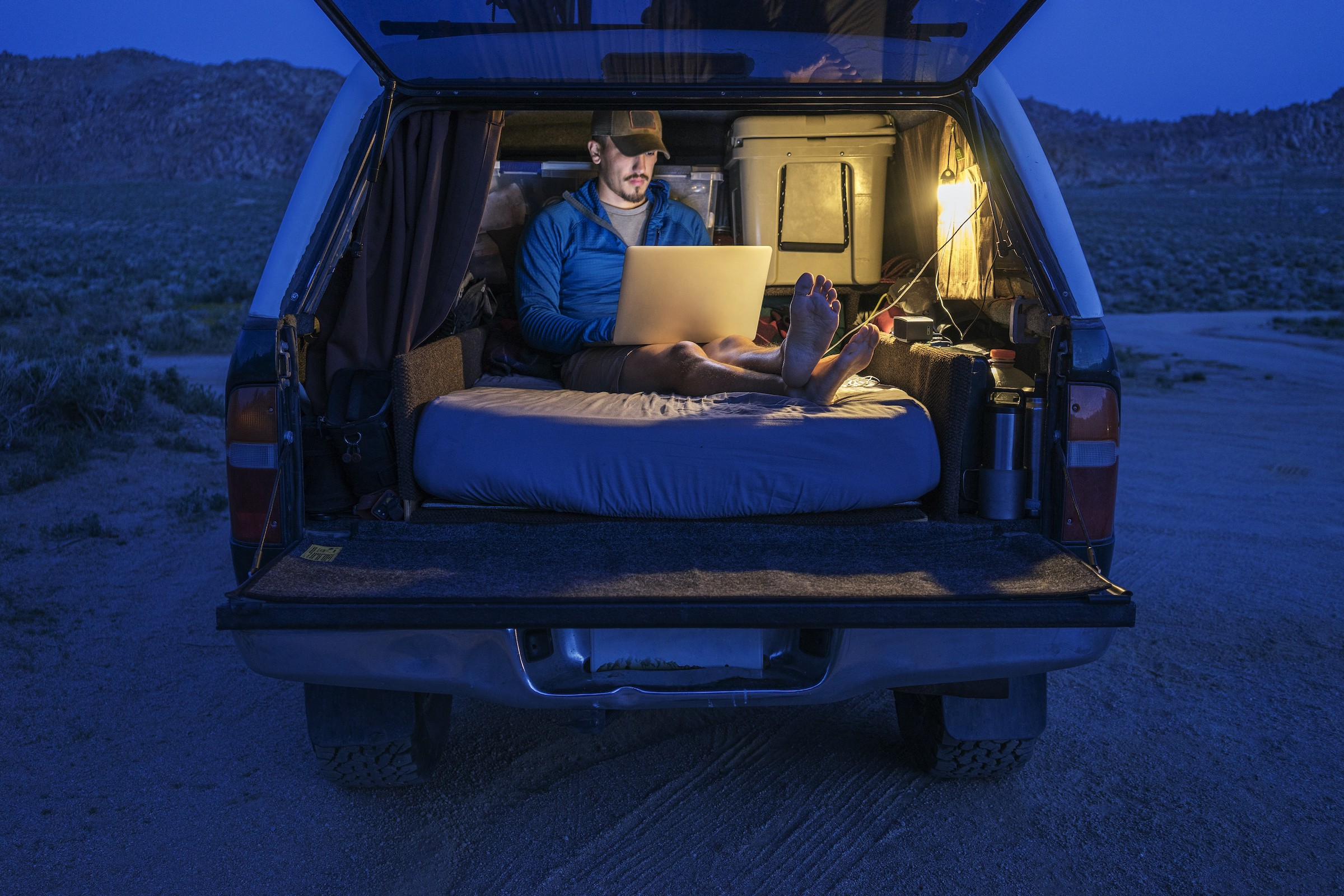 A person working on a laptop in the back of a covered pickup truck at night, sitting on a mattress.