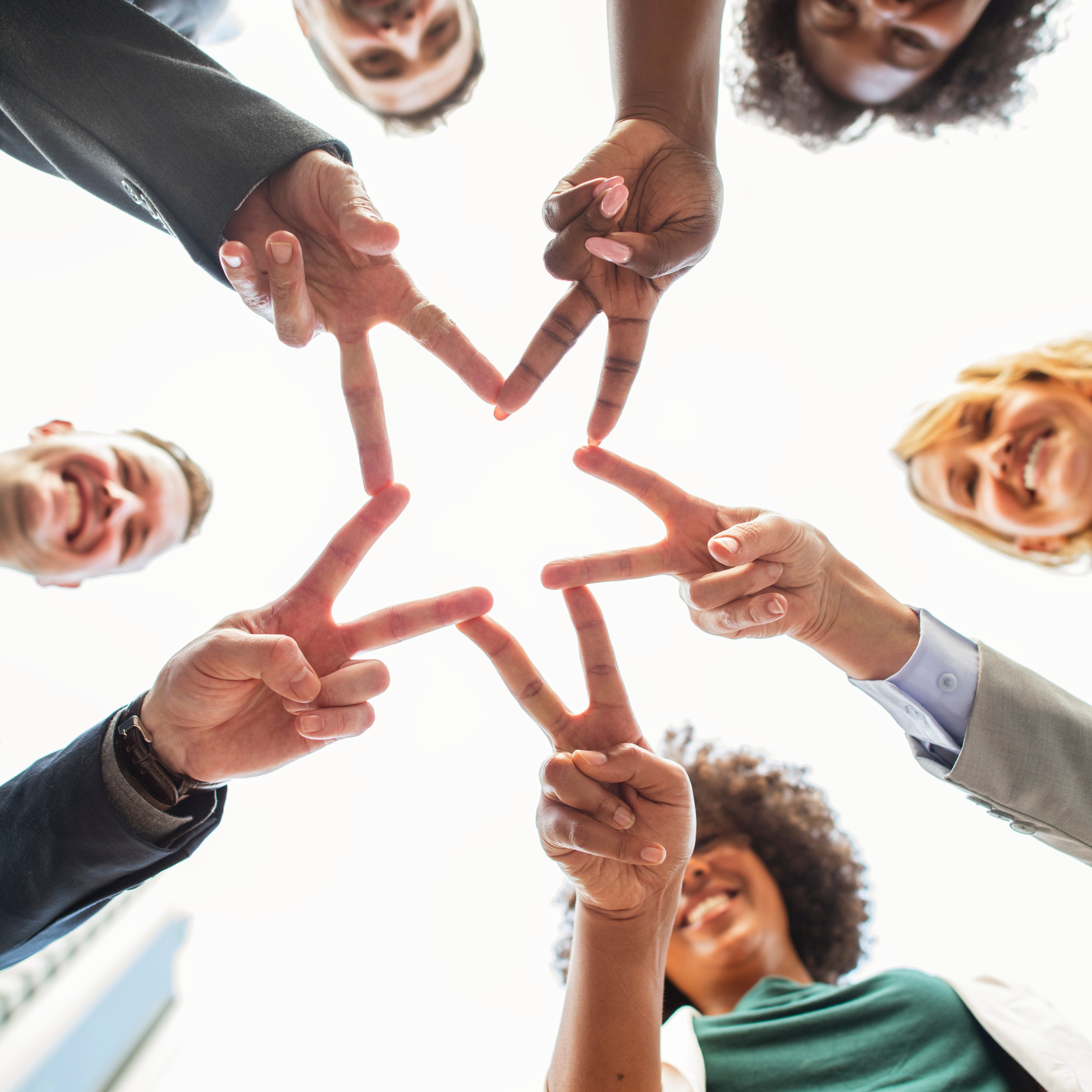 A diverse group of five people in professional attire are pictured from below as they hold out their fingers in V shapes and touch them together to form a star.