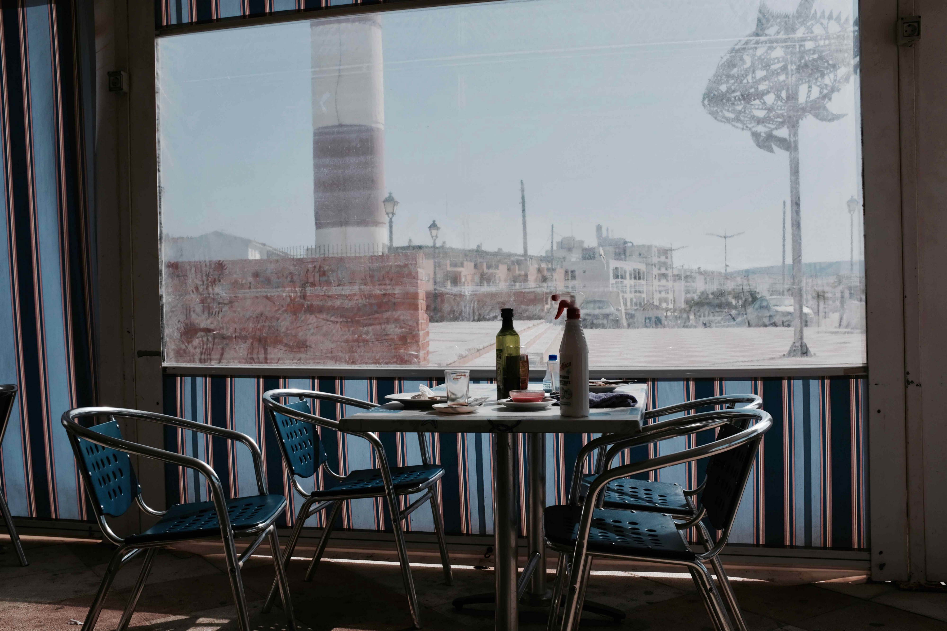 An image of a table and chairs in a cafe with the remainder of breakfast things. There is a plastic canopy around it, striped with a window and a view of a seaside front and a metal sculpture of a tuna fish.