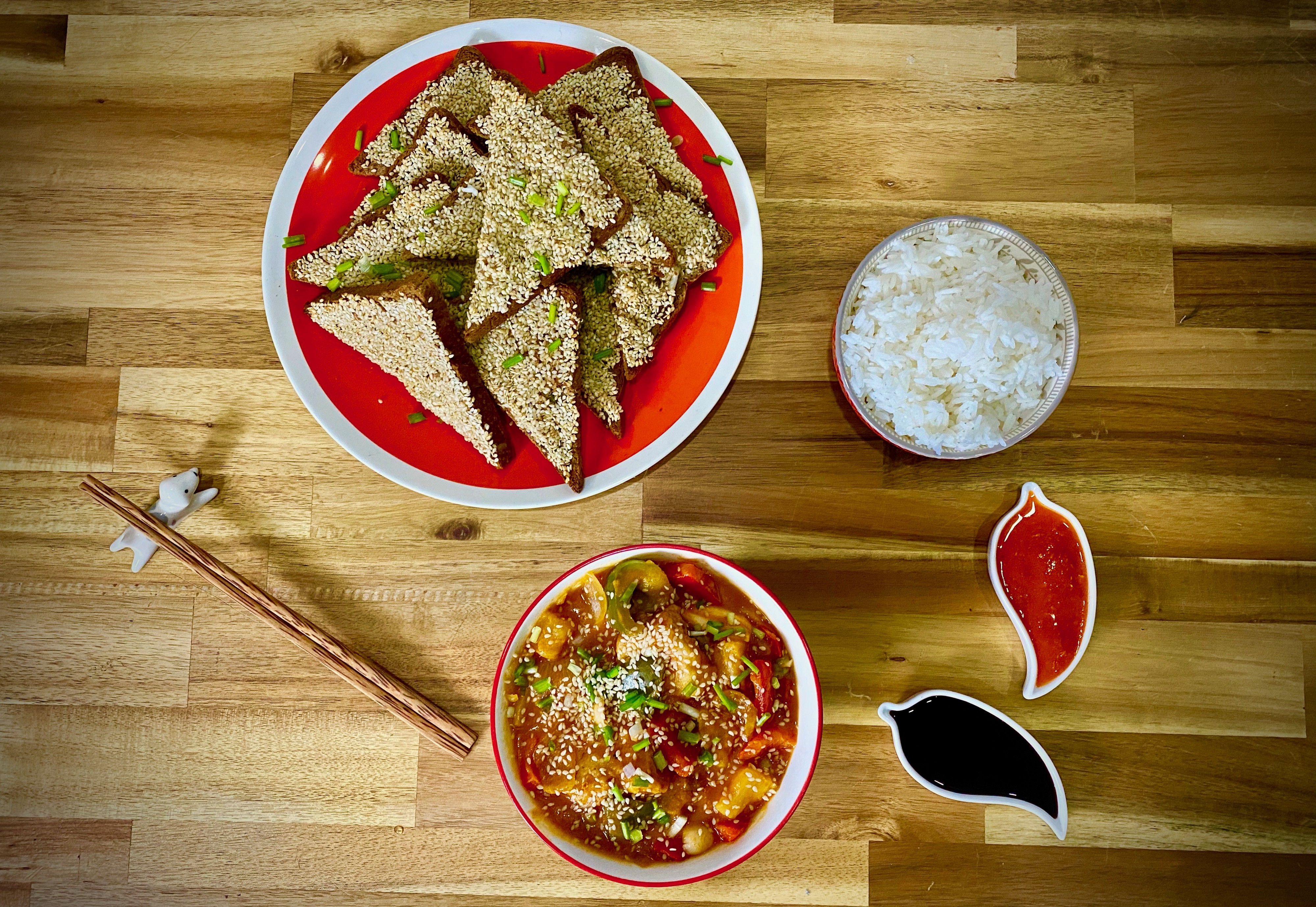 A spread of toast triangles coated in sesame seeds, warm red sweet and sour tofu, and white rice