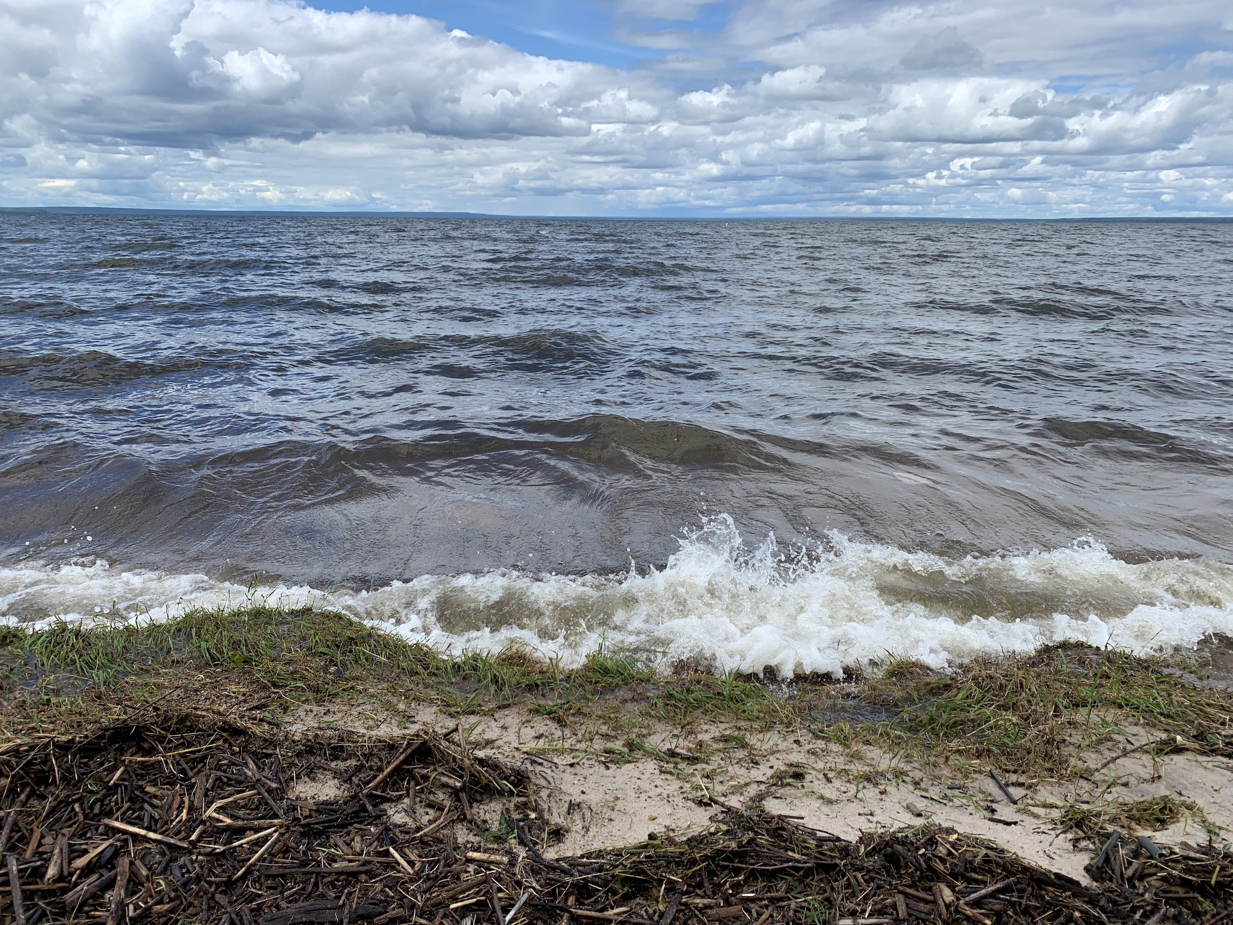 A peaceful sky in the background, lake waves crashing on the shore in the foreground.