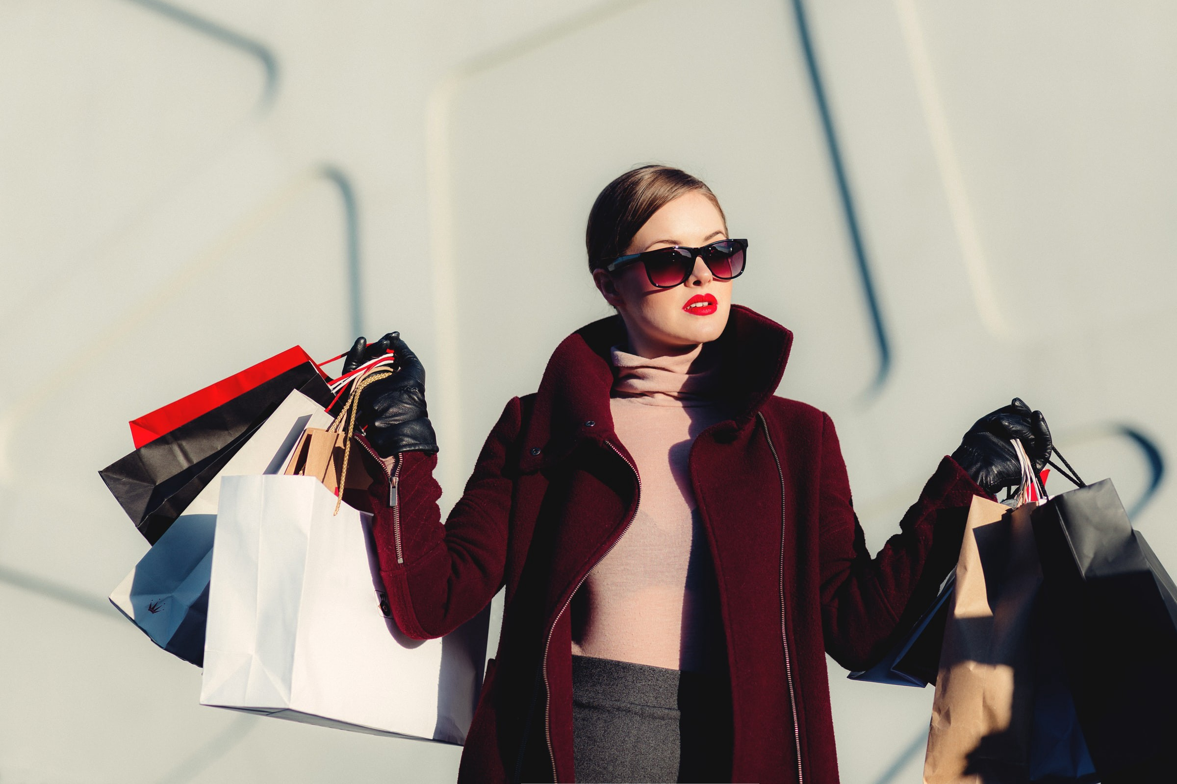 A posh nicely dressed blonde woman that just went shopping, holding multiple bags in each hand.