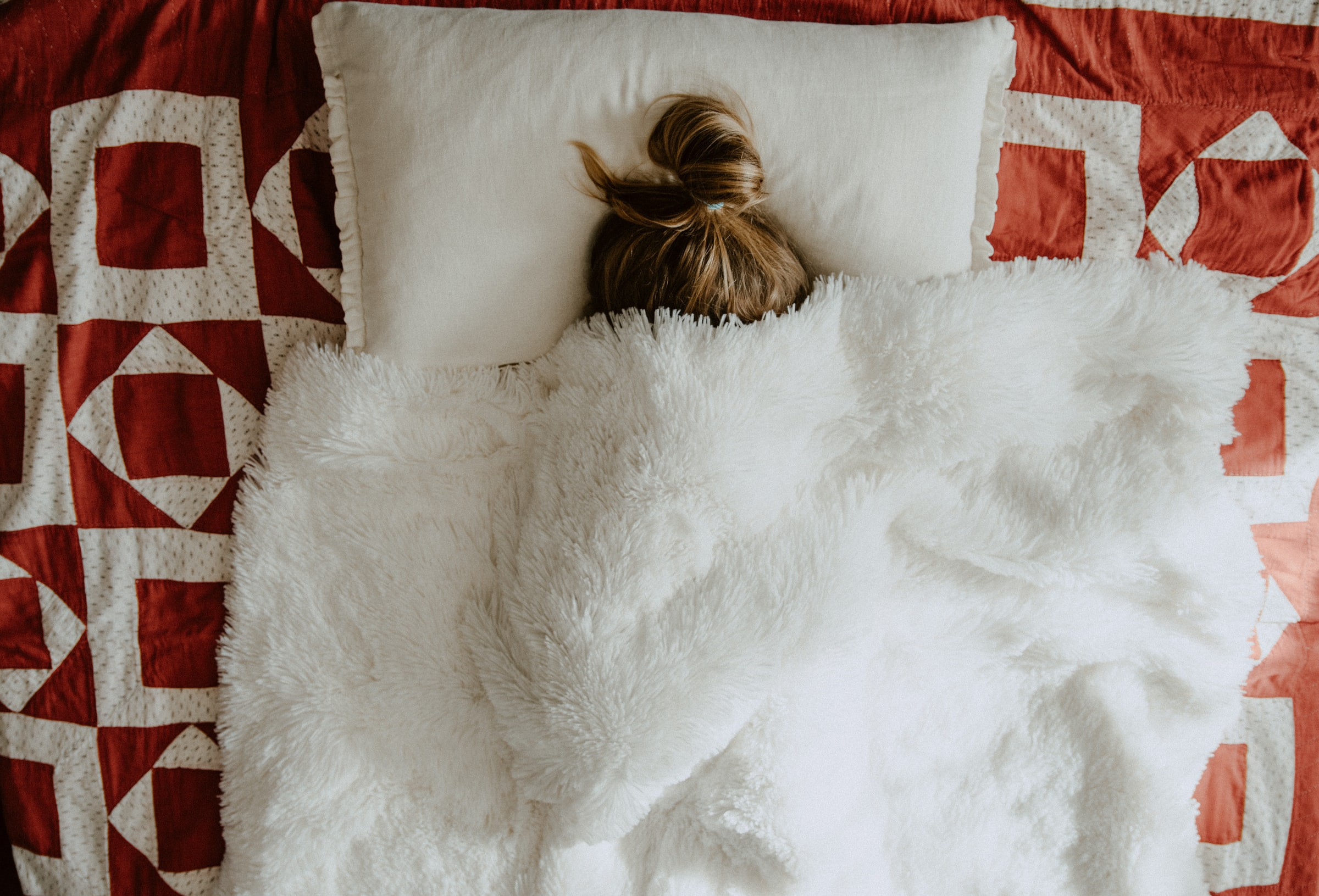Woman hides under covers on bed