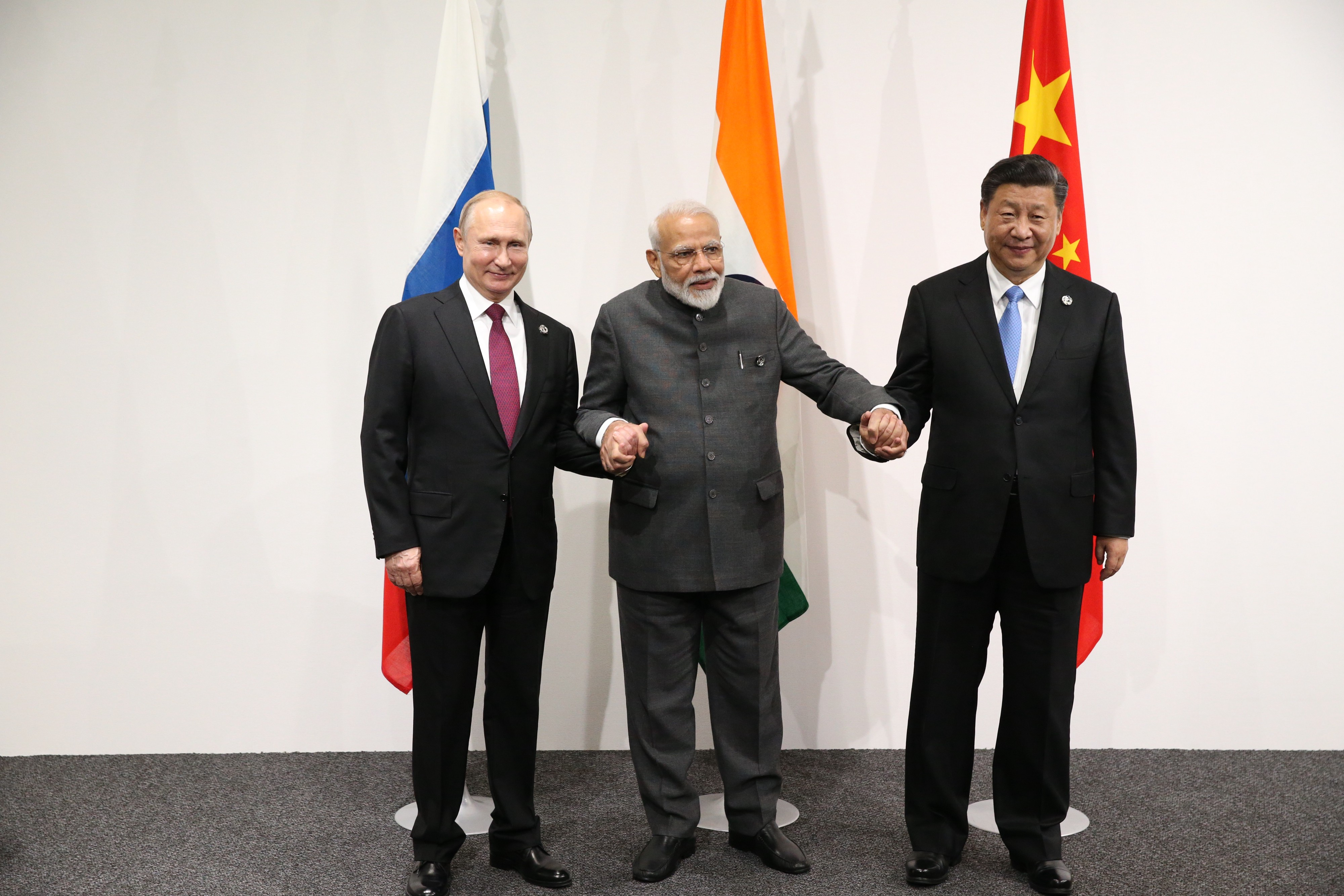 Vladimir Putin, Narendra Modi and Xi Jinping pose for a group photo prior to their trilateral meeting at the G20 Osaka Summit 2019.