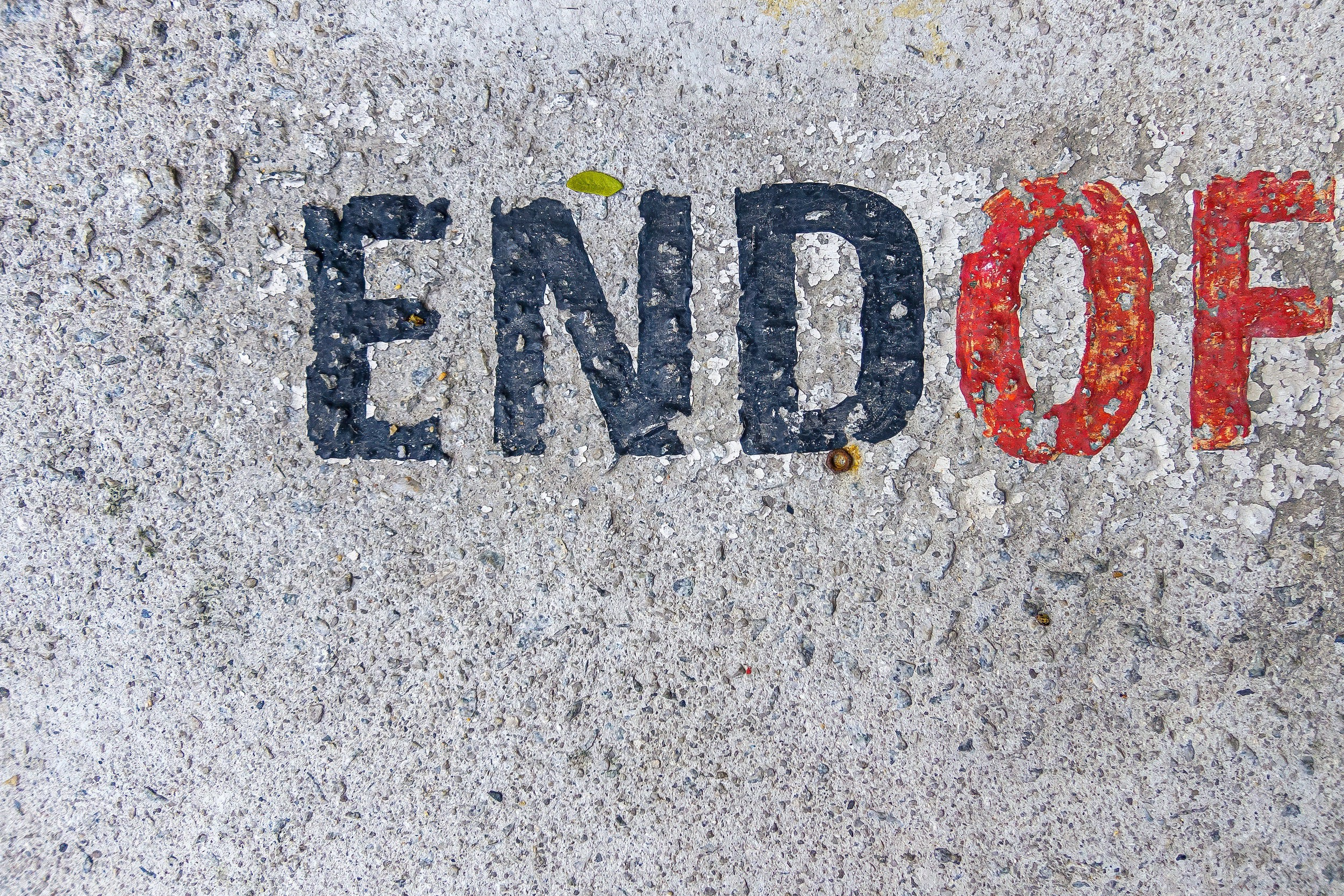 """Paint on concrete says """"End Of"""""""