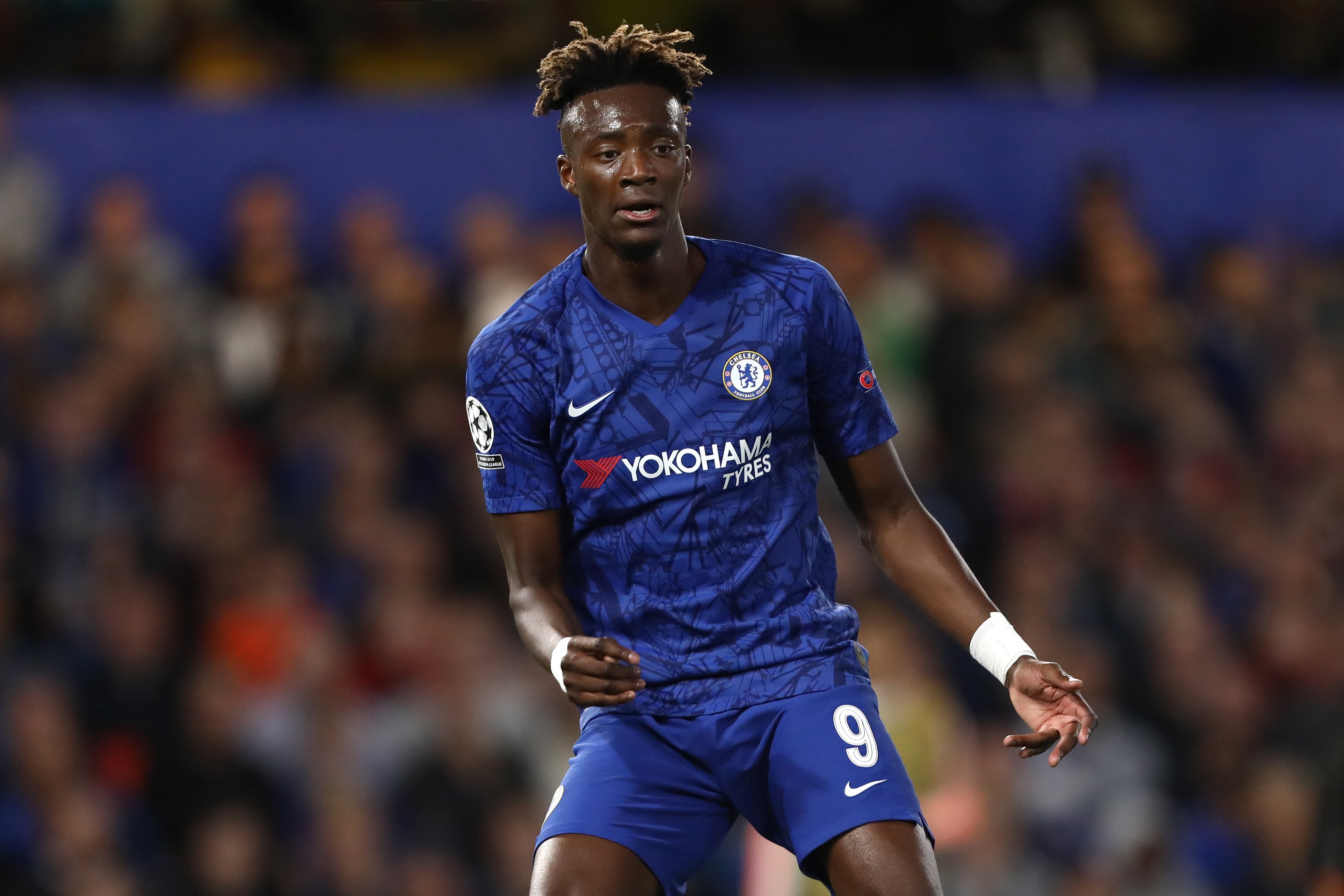 Tammy Abraham in the centre of the frame wearing Chelsea's home kit with out of focus shot of crowd in the background