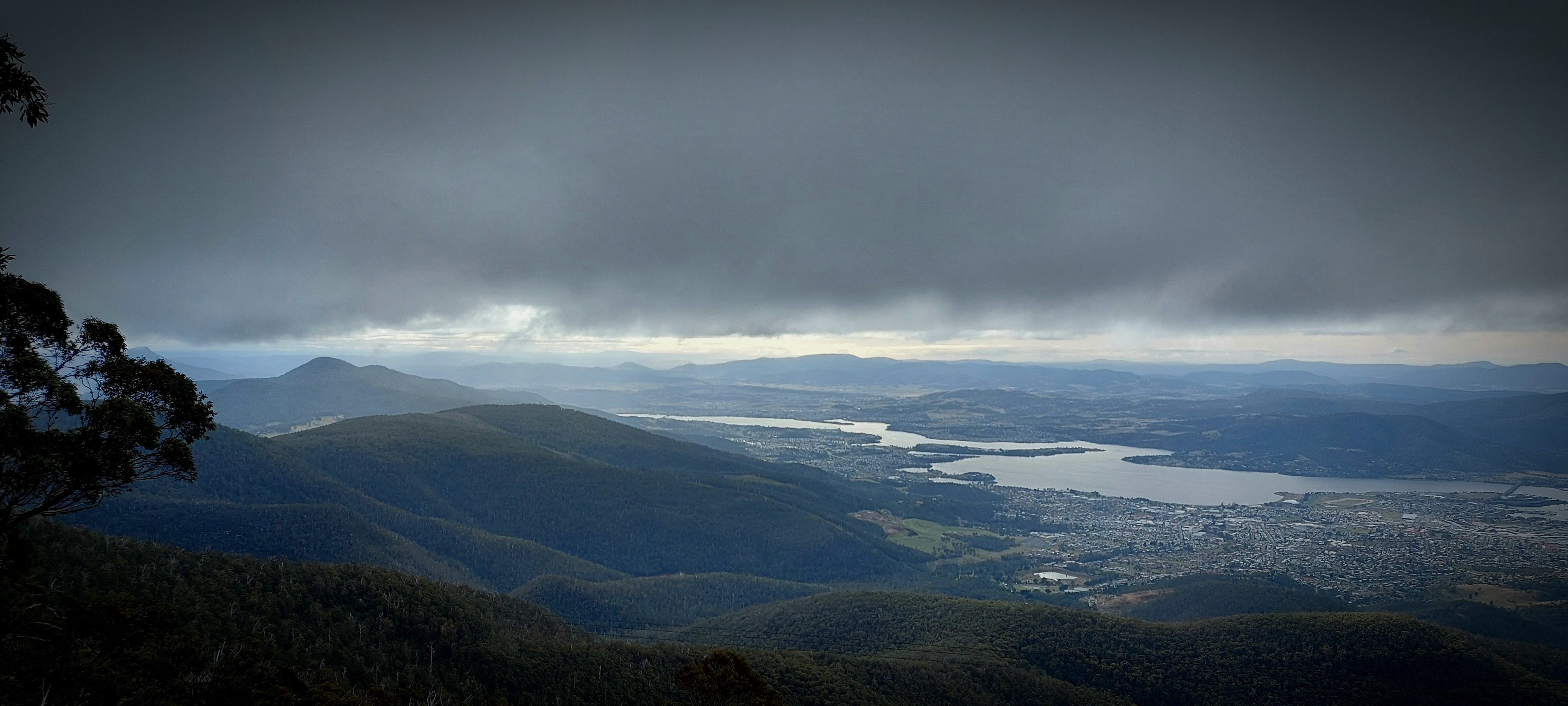 Image is a view of Hobart taken from the top of the mountain. The sky is heavy with cloud