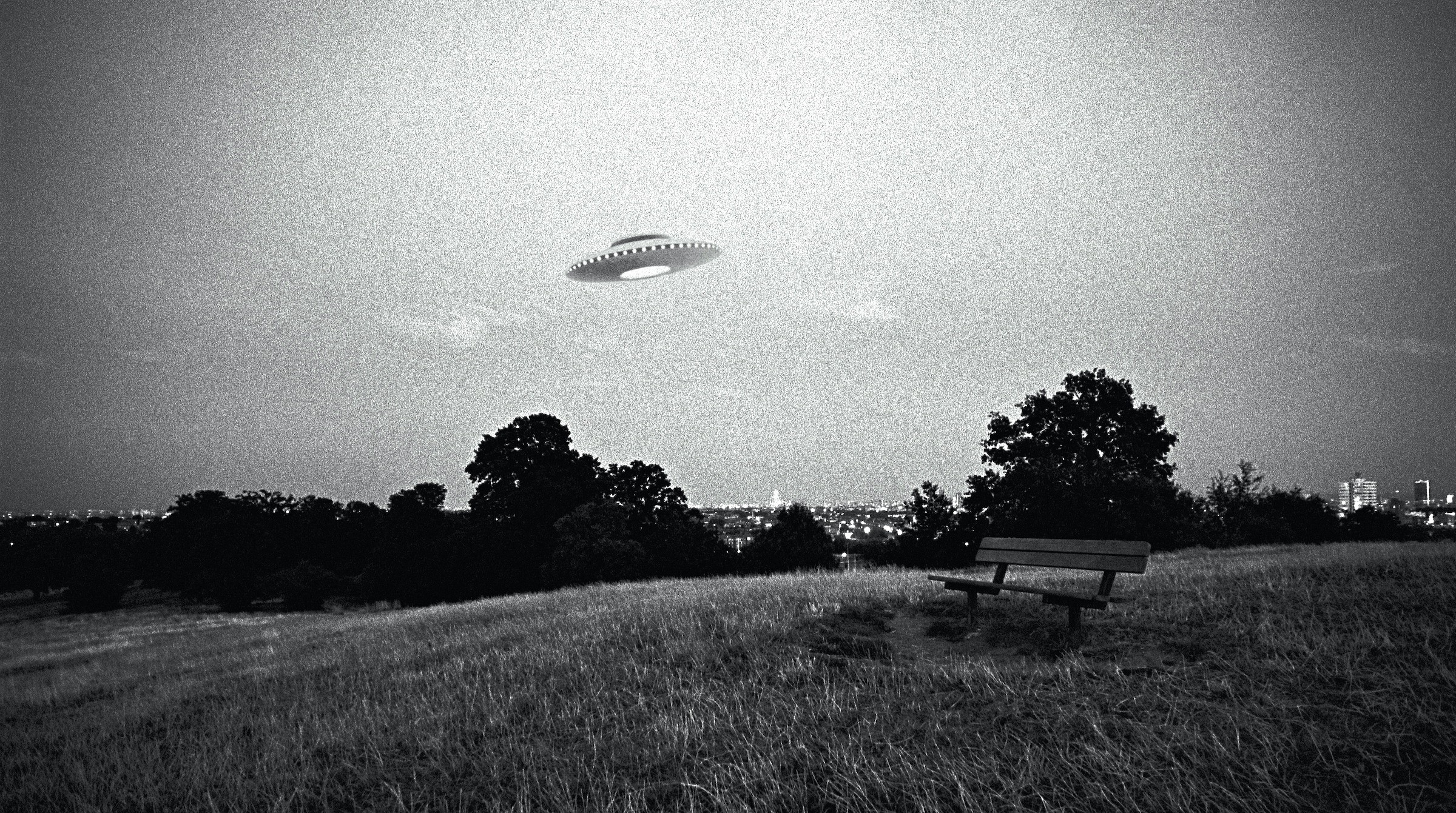 Grainy black-and-white photo of a UFO flying over a park bench overlooking an urban scene in the distance.
