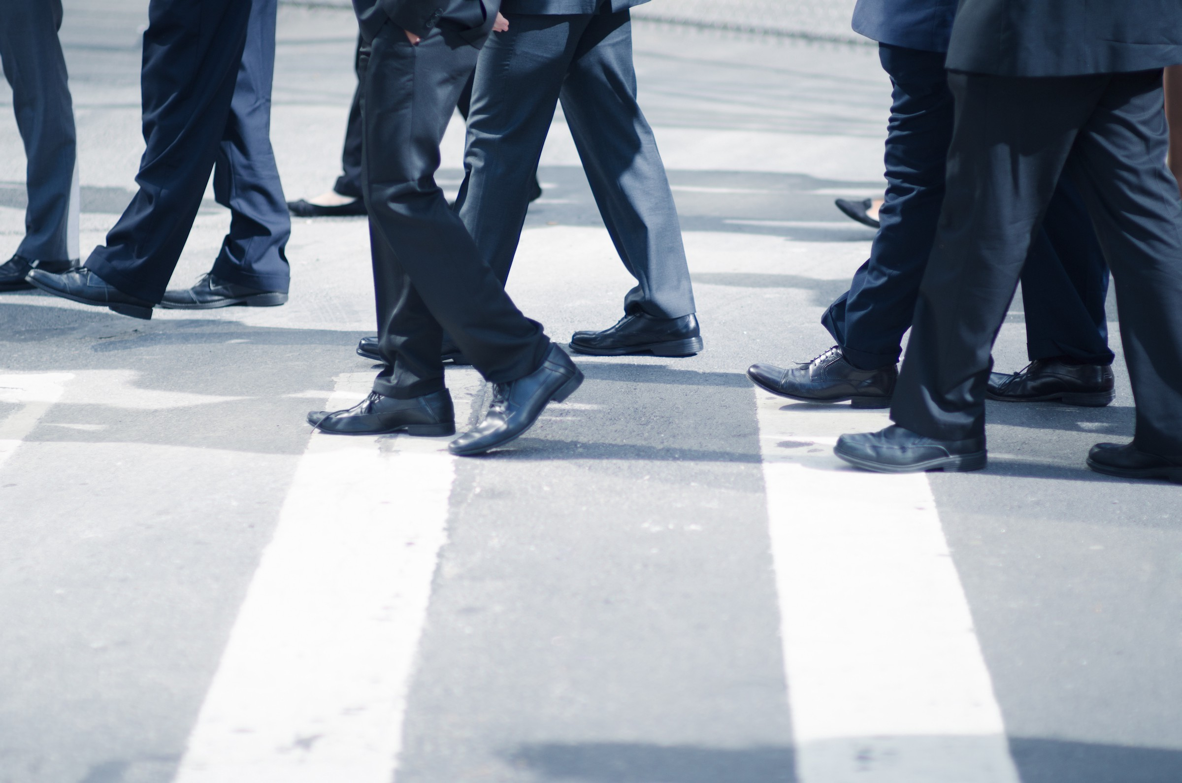 Group of businessmen in similar dark navy suits crossing a city street. You can just barely see the feet of two women.