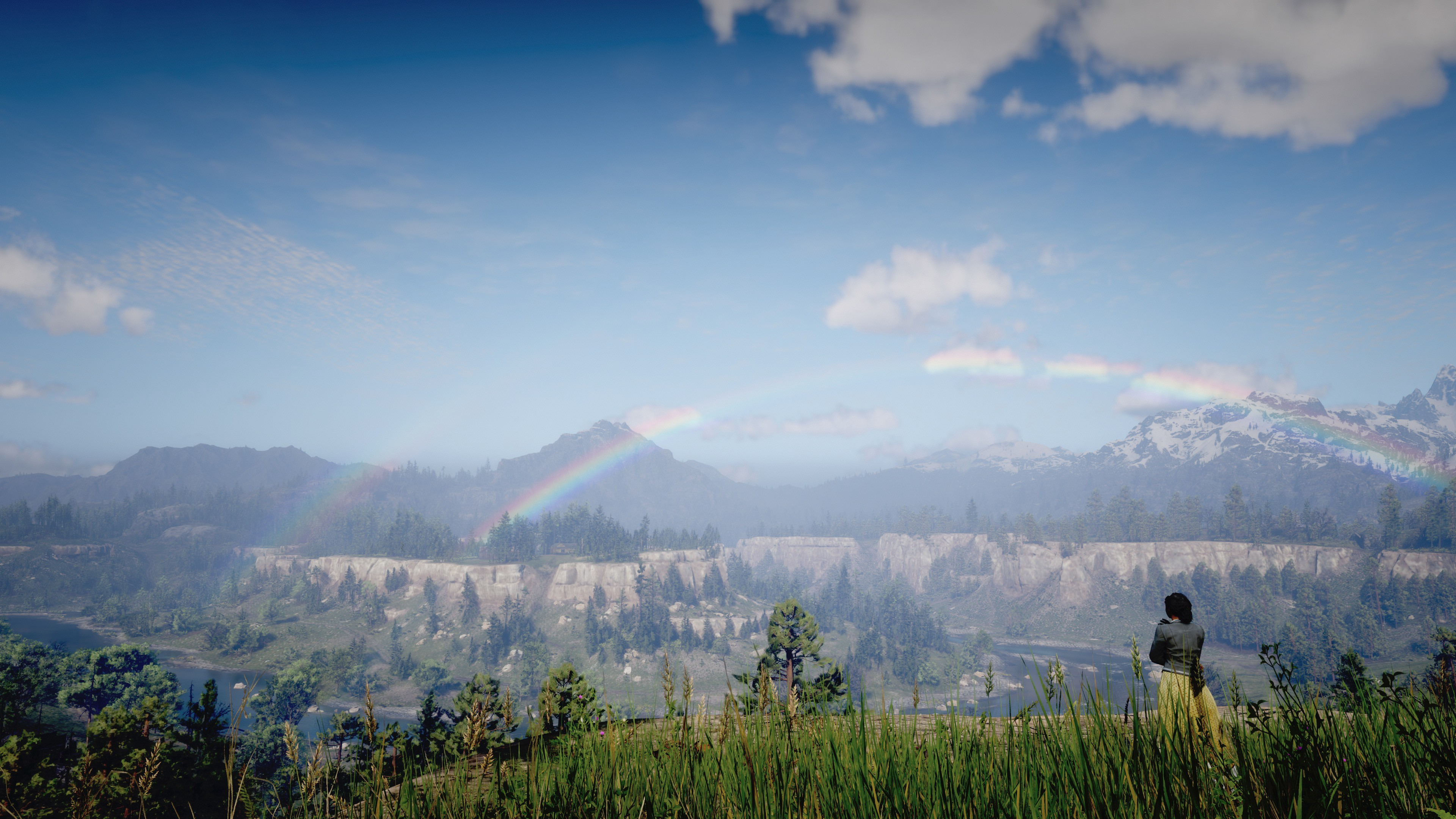 Tilly from Red Dead Redemption 2, standing at a cliffside, looking at mountains with a double rainbow above them.