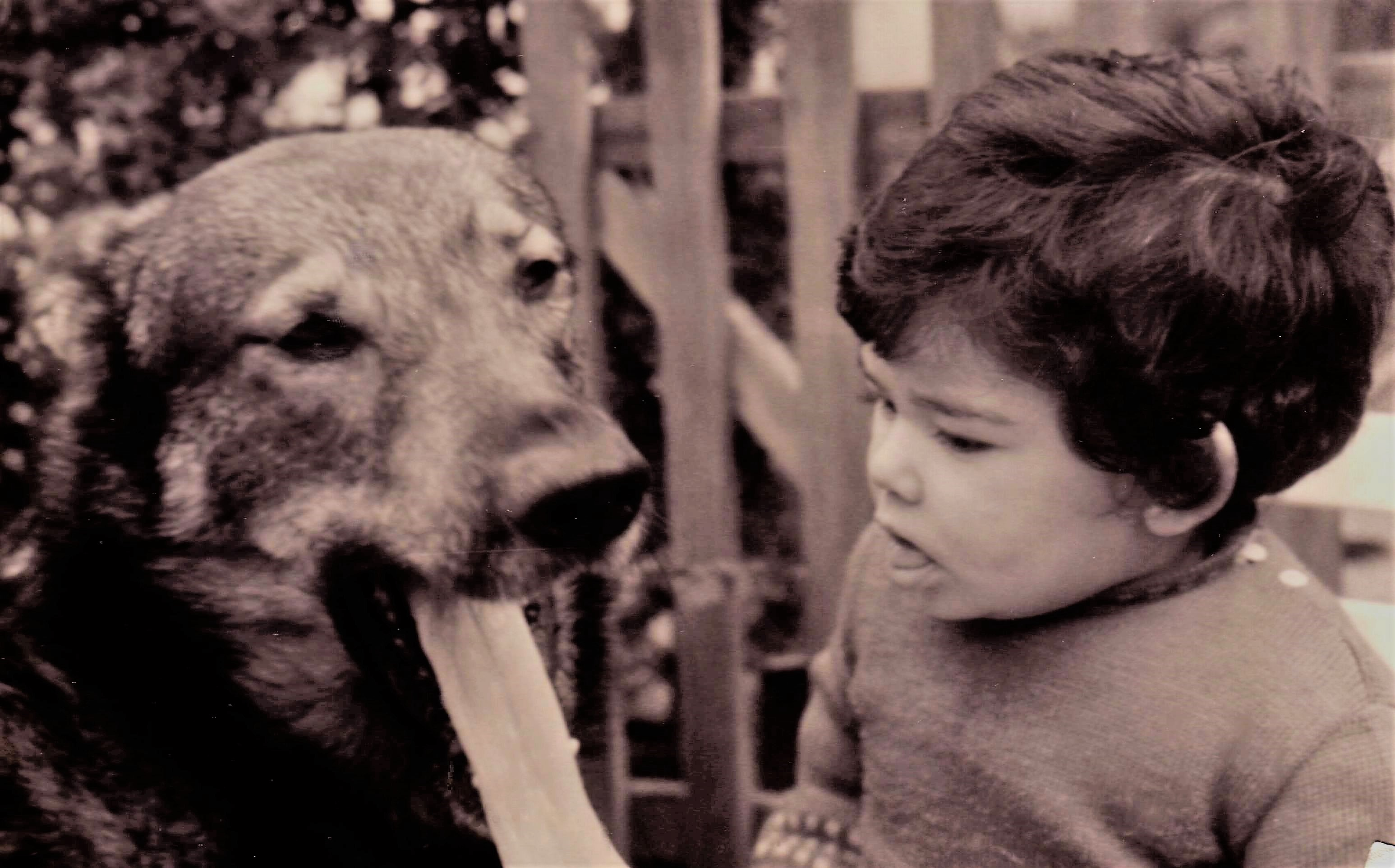 Author Vilma Reynoso as a child in Argentina sticking her tongue out with her dog, Romi.